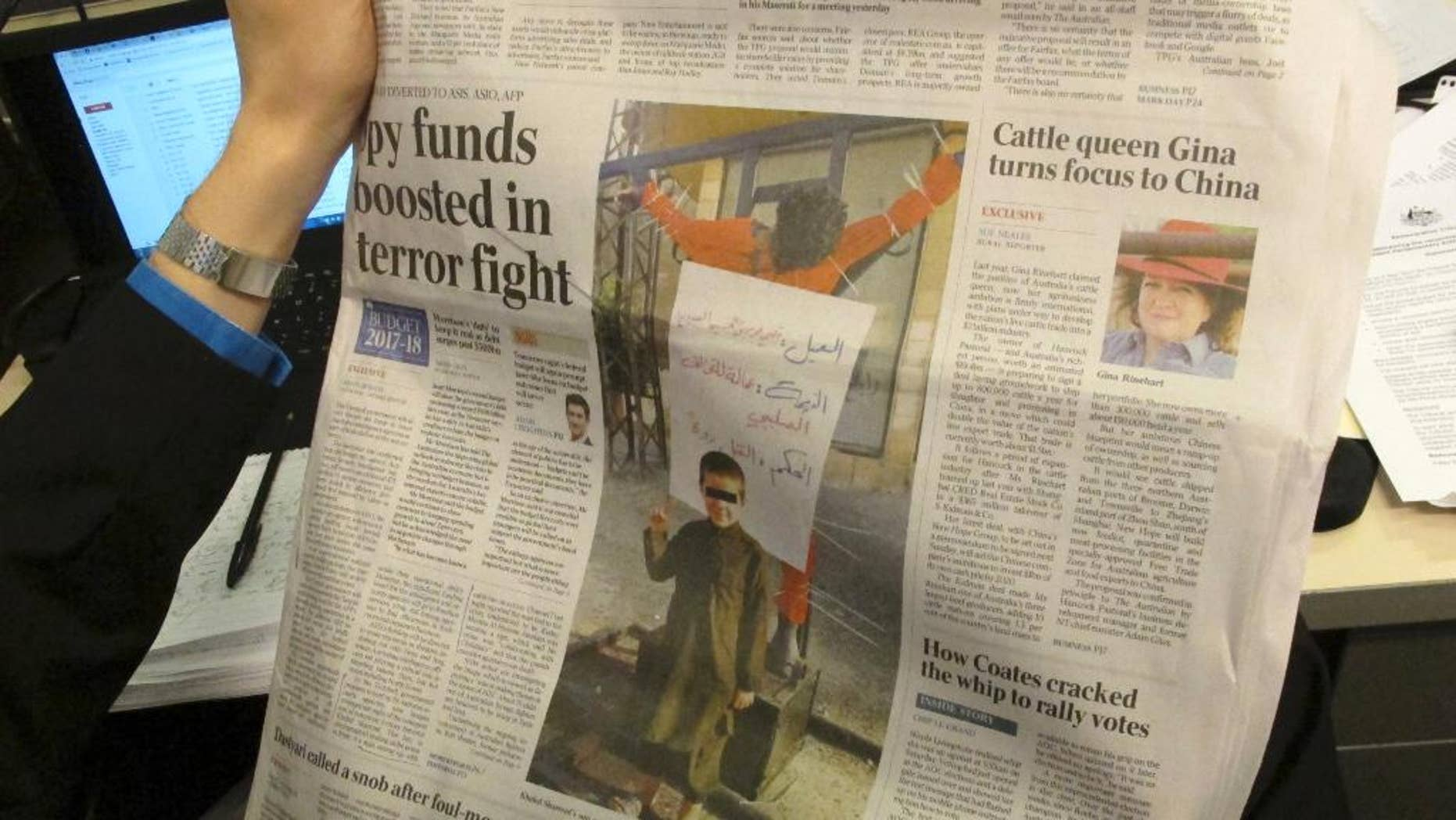 """This photo published on the front page of the Monday, May 9, 2017, edition of """"The Australian"""" newspaper shows says a 6-year-old Australian boy making an Islamic State movement salute in front of a human body hanging from a cross somewhere in the Middle East, in Canberra. Australian Prime Minister Malcolm Turnbull said on Monday such children who returned from the battle fields of Syria and Iraq would be subjected to """"the closest attention"""" to ensure Australian are safe. (AP Photo/Rod McGuirk)"""