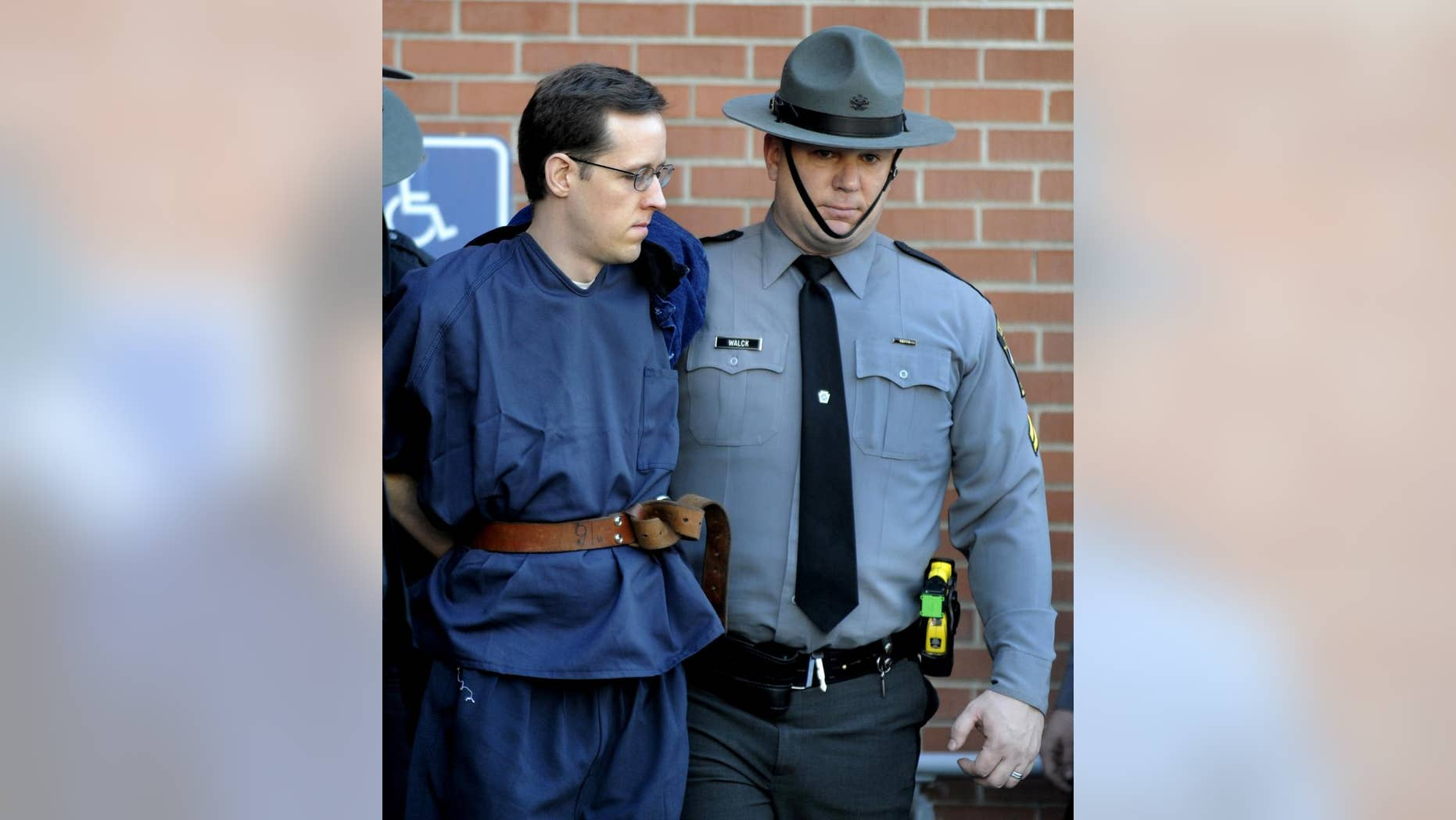 FILE- In this Jan. 5, 2015, file photo, Eric Frein, left, is led from the Pike County Courthouse after his preliminary hearing in Milford, Pa. Frein is charged with fatally shooting a Pennsylvania state trooper and wounded another during an ambush at their barracks in September. A formal arraignment for Frein is scheduled for Thursday, Jan. 29, 2015, at the courthouse in Milford. (AP Photo/David Kidwell, File)