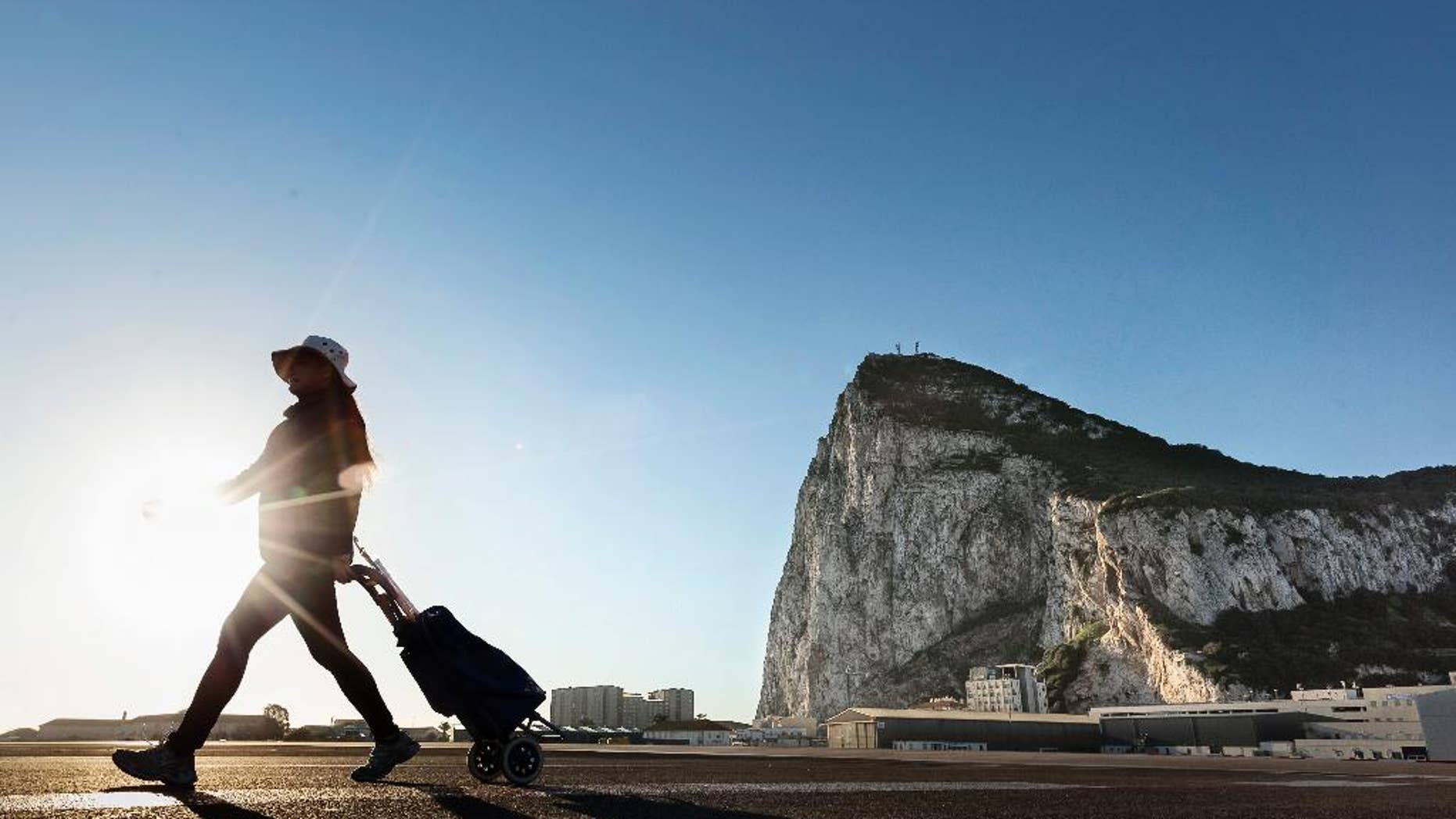 FILE- In this Wednesday, March 1, 2017 file photo, a woman walks on the Spanish side of the border between Spain and the British overseas territory of Gibraltar with the Rock of Gibraltar in the background, in La Linea de la Concepcion, Spain. Deep inside the Rock of Gibraltar is a room known as The Vault. Dug by the British army in World War Two, the room now houses servers that power the websites of dozens of international online gambling companies. Those companies were lured to this speck of British territory on Spain's southern tip by its low taxes and its unimpeded access to the European Union's single market of around 500 million people. Britain's looming departure from the EU, therefore, has cast a cloud over Gibraltar's future because Brexit could see it shut off from the rest of the EU.(AP Photo/Daniel Ochoa de Olza, File)