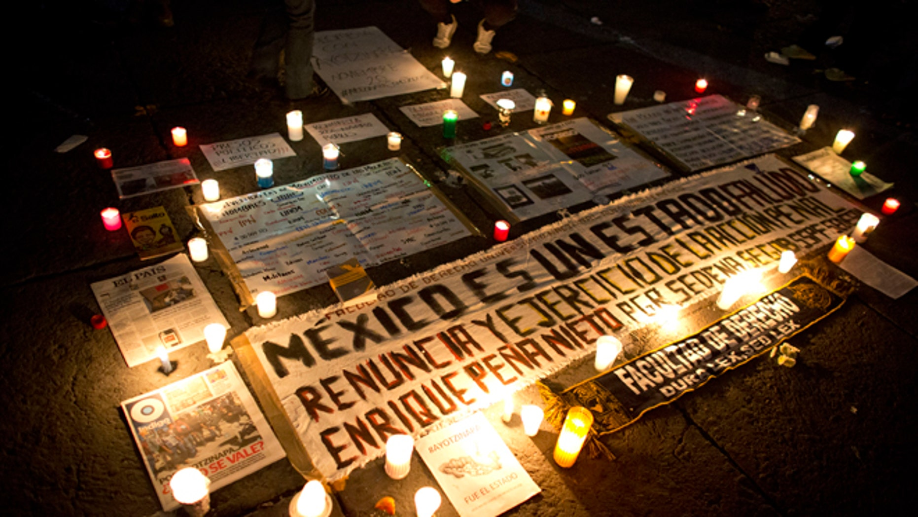 Candles surround protest signs carried by demonstrators in a march against the disappearance of 43 college students. Protesters marched in Mexico City to demand authorities find the missing students. (AP Photo/Rebecca Blackwell)