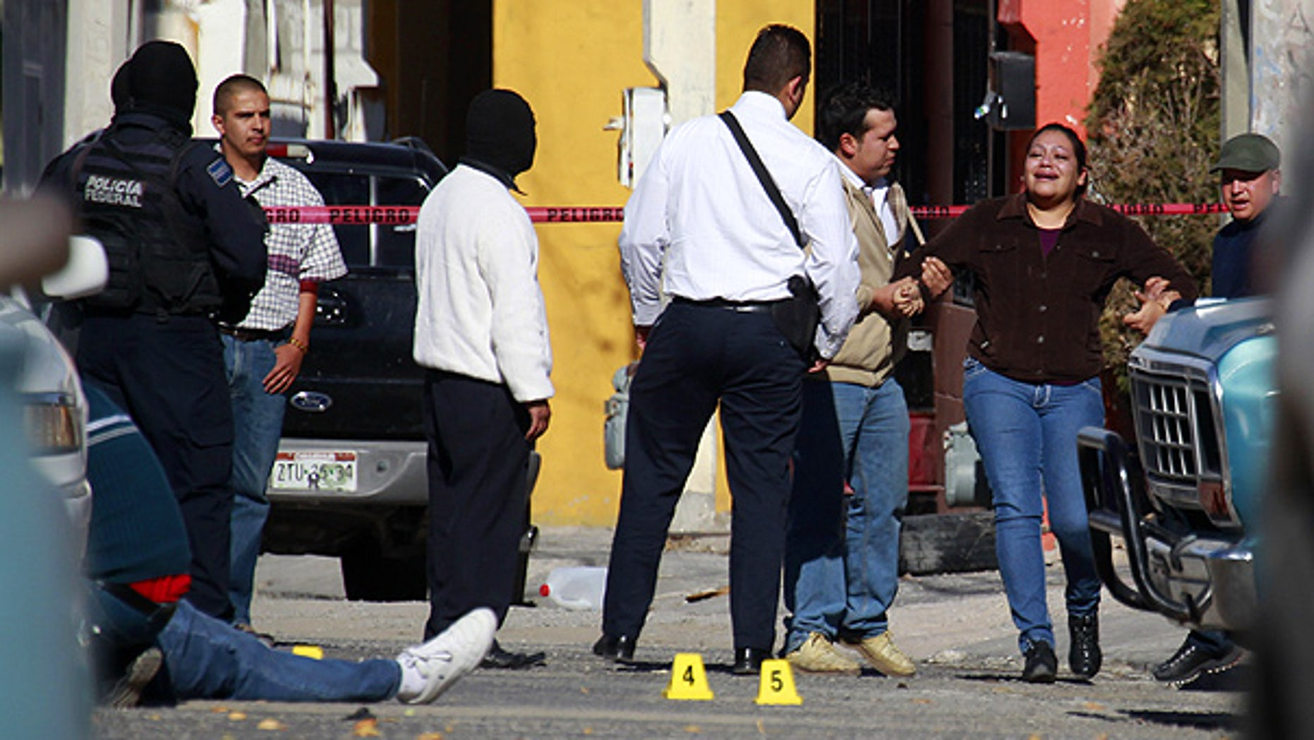 Dec. 14: A woman is held back by police as she reacts while seeing a relative dead lying on the ground after he and another man were killed by gunmen in the northern border city of Ciudad Juarez, Mexico.