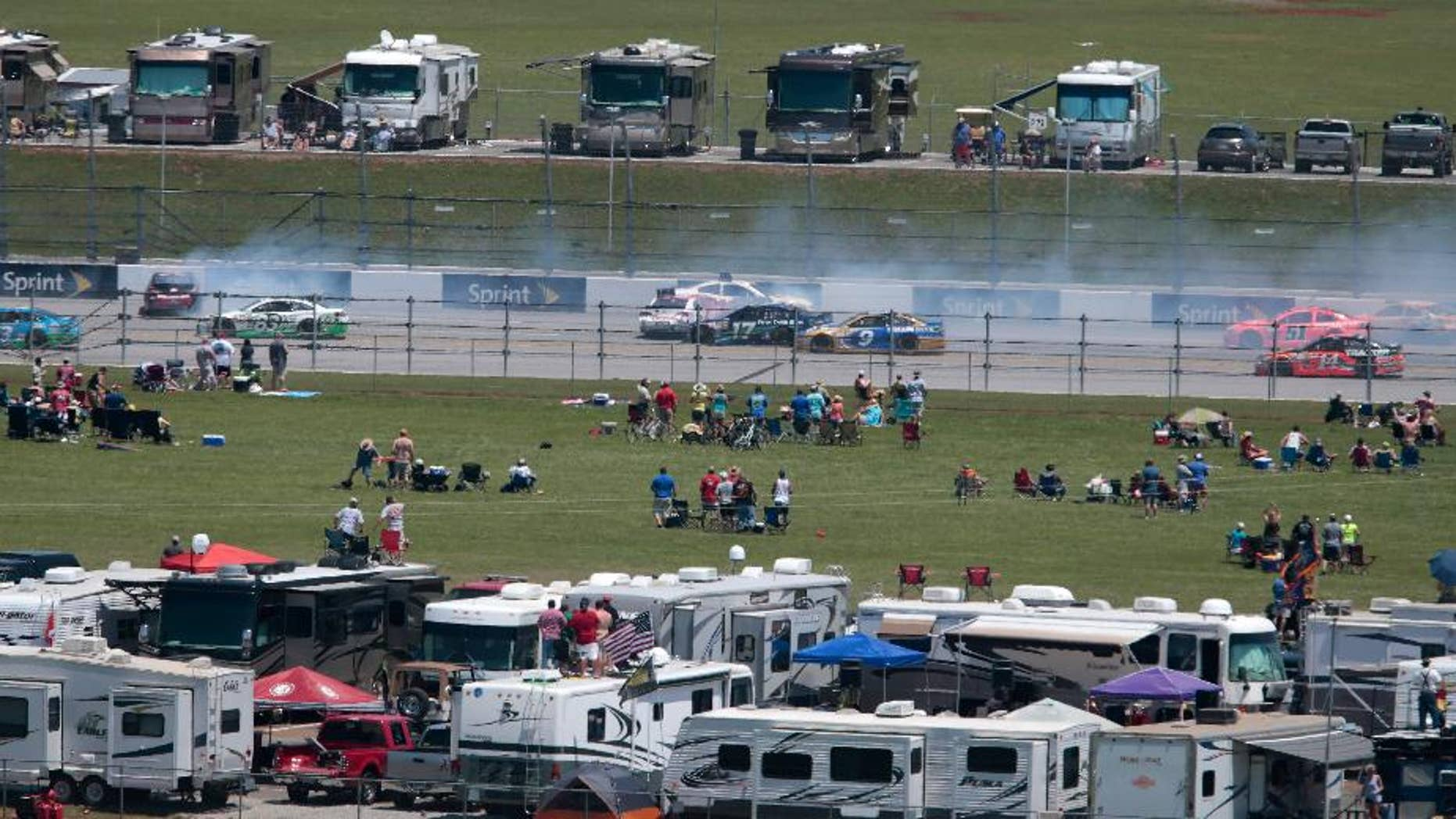 Fans watch a multi-car crash on the back straight during the Talladega 500 NASCAR Sprint Cup Series auto race at Talladega Superspeedway, Sunday, May 3, 2015, in Talladega, Ala. (AP Photo/Butch Dill)