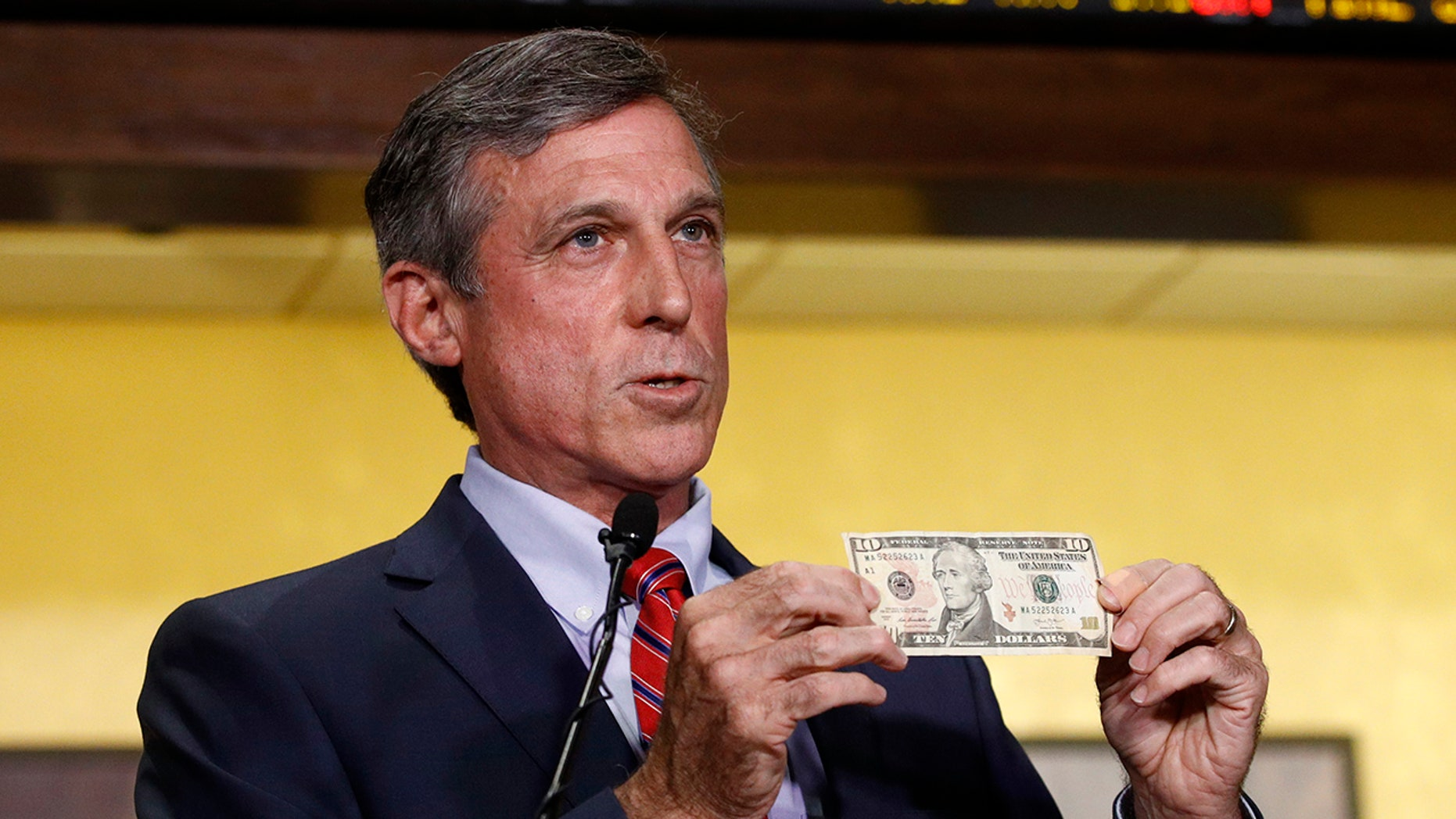 Delaware Gov. John Carney displays a ten dollar bill before using it to place a bet on a baseball game between the Chicago Cubs and the Philadelphia Phillies.