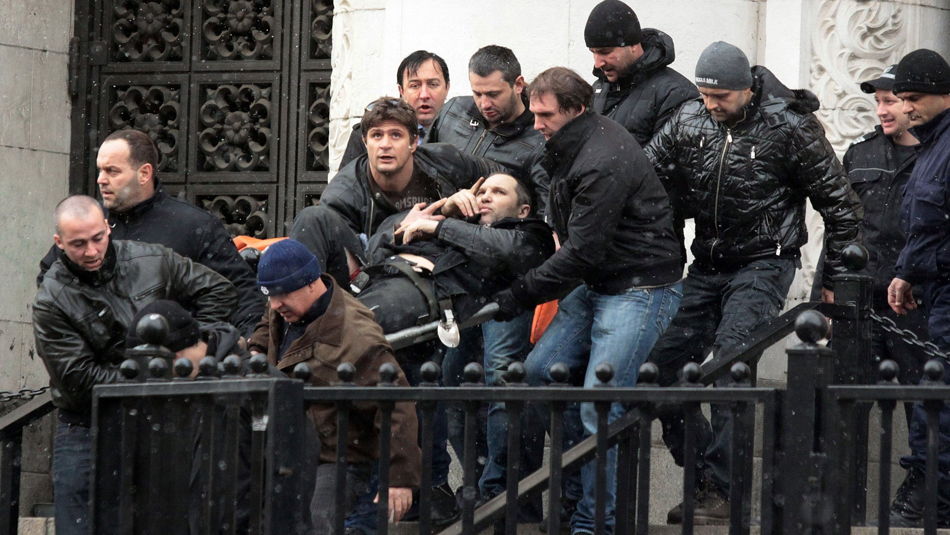 Bodyguards carry Zlatomir Ivanov, after he was shot in front of central court house in downtown Sofia, Tuesday, Jan. 29, 2013. Unidentified gunmen have shot and seriously wounded Zlatomir Ivanov who is alleged to be an underworld boss. Convicted underworld boss, Zlatomir Ivanov was on his way to the Sofia Court House on Tuesday when the shooter opened fire, probably from an opposite building, a senior police officer said. Ivanov and one of his bodyguards were both hit as they walked up the stairs to enter the court. Police say Ivanov was undergoing surgery after suffering four gunshots. (AP Photo)