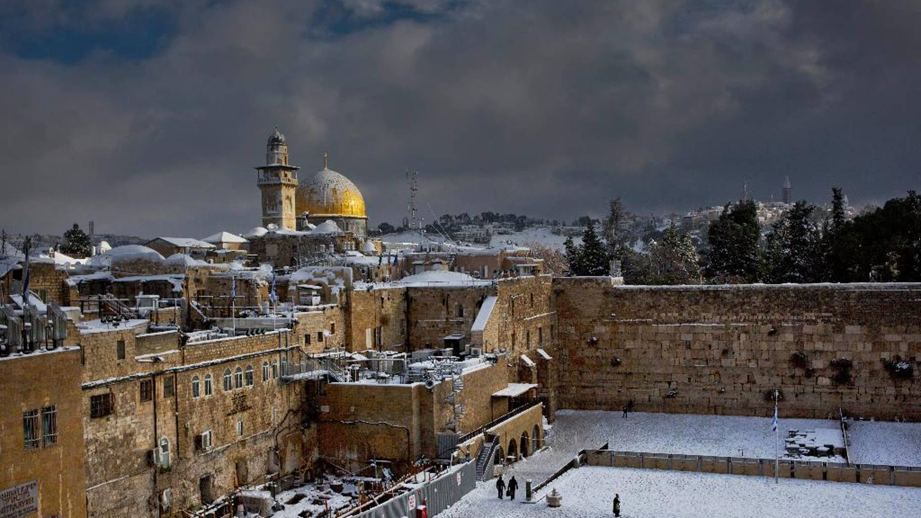 FILE - In this Dec. 13, 2013 file photo, the Western Wall, right, and the gilded Dome of the Rock, among the holiest sites for Jews and Muslims, are covered in snow. Two Palestinians stormed a Jerusalem synagogue on Tuesday, Nov. 18, 2014 attacking worshippers praying inside with knives, axes and guns, and killing four people before they were killed in a shootout with police, officials said. (AP Photo/Dusan Vranic, File)