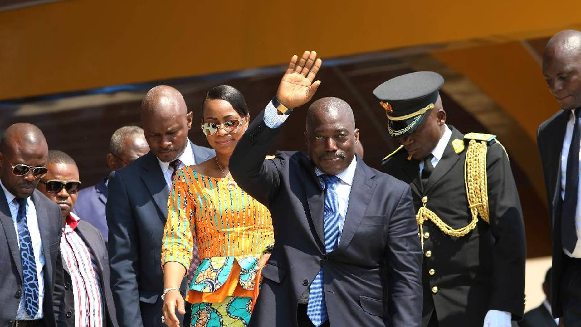 FILE- In this Thursday, June 30, 2016 file photo, Congolese President Joseph Kabila, center, waves as he and others celebrate the Democratic Republic of Congo, DRC, independence in Kindu, Congo. Congo's ruling party is proposing an interim unity government with the opposition as an election set for November, 2016, now seems nearly impossible, though President Joseph Kabila would remain in charge, the country's justice minister said. (AP Photo/John Bompengo, File)