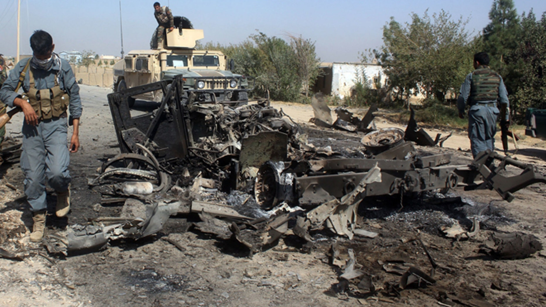 FILE: Afghan security forces inspect the site of a U.S. airstrike in Kunduz city.