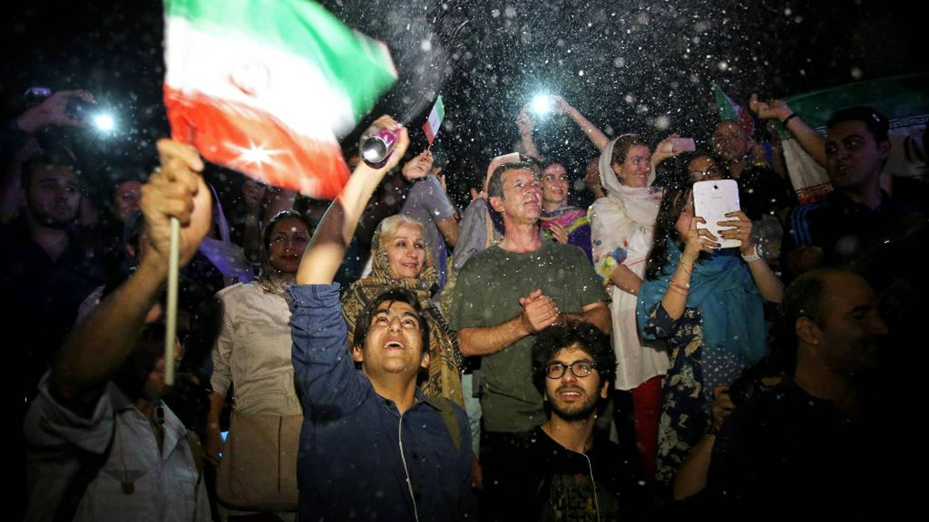 A group of jubilant Iranians cheer and spray artificial snow during street celebrations following a landmark nuclear deal, in Tehran, Iran, Tuesday, July 14, 2015. After long, fractious negotiations, world powers and Iran struck an historic deal Tuesday to curb Iran's nuclear program in exchange for billions of dollars in relief from international sanctions - an agreement aimed at averting the threat of a nuclear-armed Iran and another U.S. military intervention in the Middle East. (AP Photo/Ebrahim Noroozi)