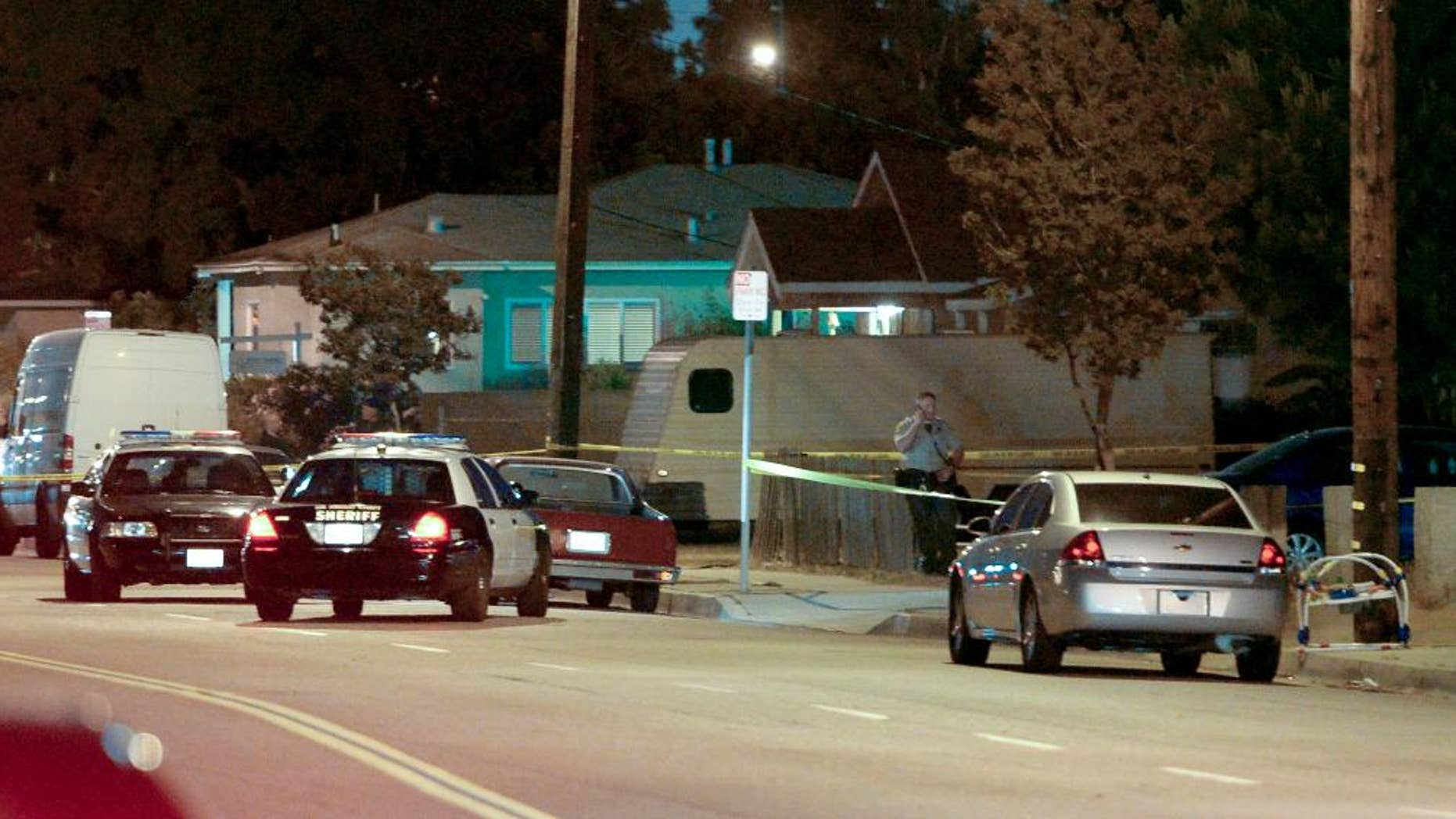 Los Angeles County sheriff's deputies block off the scene of a triple homicide that occurred in the unincorporated area of Los Angeles, Calif., Tuesday, May 20, 2014.  Carol Coronado, 30, was arrested on suspicion of murder, taken to a hospital for examination and then to a sheriff's station for booking. Authorities say she made no statement. (AP Photo/The Daily Breeze, Steve McCrank)