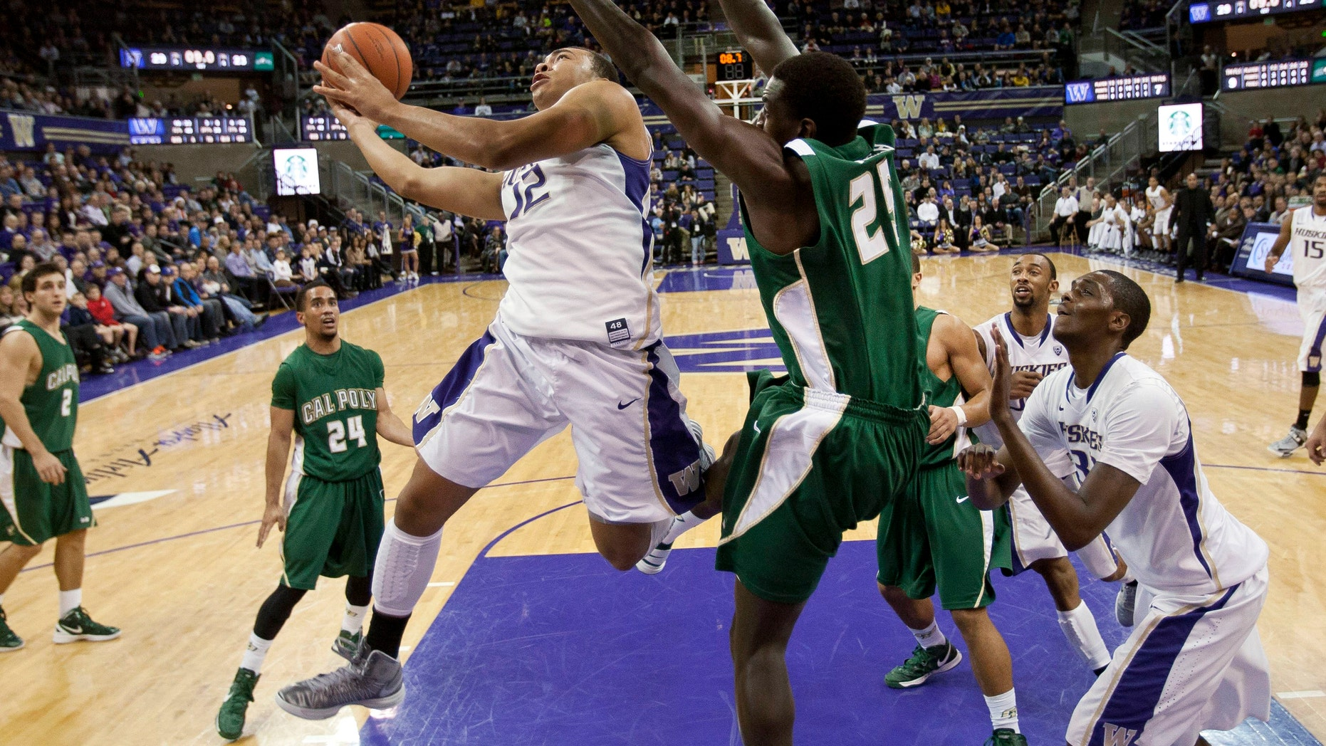Washington's Andrew Andrews slides around Cal Poly's Joel Awich to score during the first half of an NCAA college basketball game, Thursday, Dec. 20, 2012, in Seattle. (AP Photo/The Seattle Times, Dean Rutz) MAGS OUT; NO SALES; SEATTLEPI.COM OUT; MANDATORY CREDIT.