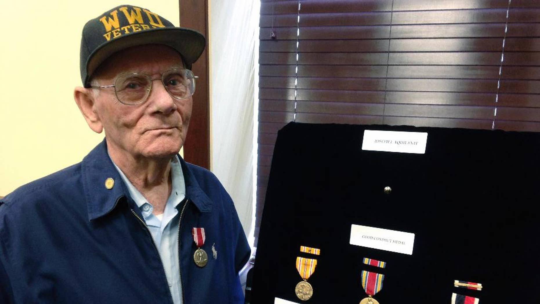 World War II veteran Joseph Aquilante, 91, of North Providence, R.I., stands beside medals presented to him by U.S. Sen. Jack Reed, Monday, May 15, 2017, at the senator's office in Cranston, R.I. Joseph Aquilante, of North Providence, sought the medals so he could leave them for his grandchildren and great-grandchildren. He says he wants to pass them on as a keepsake and part of history. (AP Photo/Jennifer McDermott)