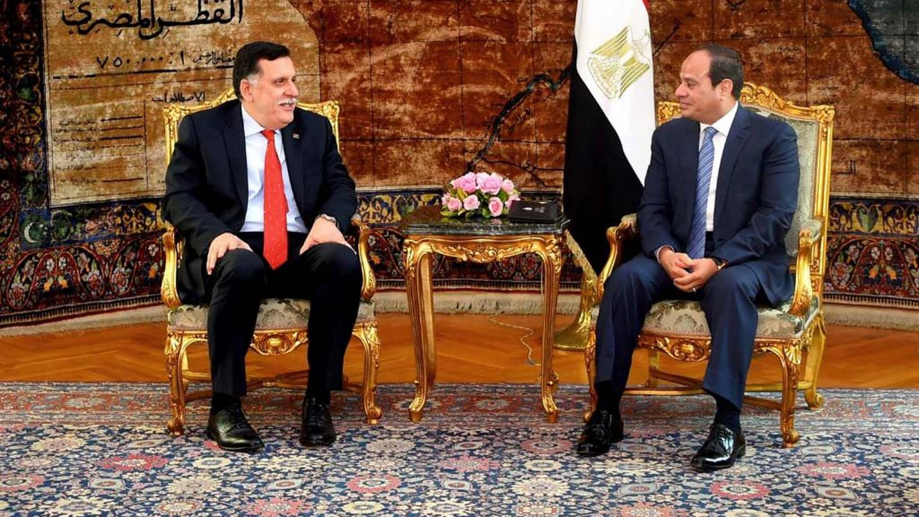 In this photo released by the Egyptian Presidency, Libyan Prime Minister Fayez al-Serraj, left, meets with Egyptian President Abdel-Fattah el-Sissi in Cairo, Egypt, Sunday, May 8, 2016. Libya's new prime minister called on the international community to help the country bolster its fight against terrorism on Sunday, urging the lifting an arms embargo and release of funds that remain frozen under U.N. sanctions. (Egyptian Presidency via AP)
