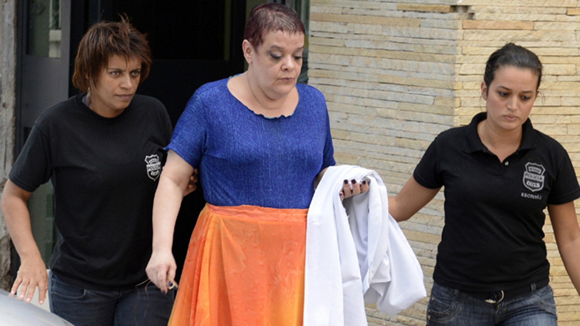 """Feb. 19, 2013: In this photo, Virginia Helena Soares de Souza, center, is escorted by police officers to a temporary prison in Curitiba, Parana state, Brazil. According to Brazil's health ministry, Soares de Souza, who's a medical doctor, and seven assistants are suspected of killing seven terminally ill patients in a southern Brazilian hospital, injecting them with """"drug cocktails"""" and of tampering with their respirators."""