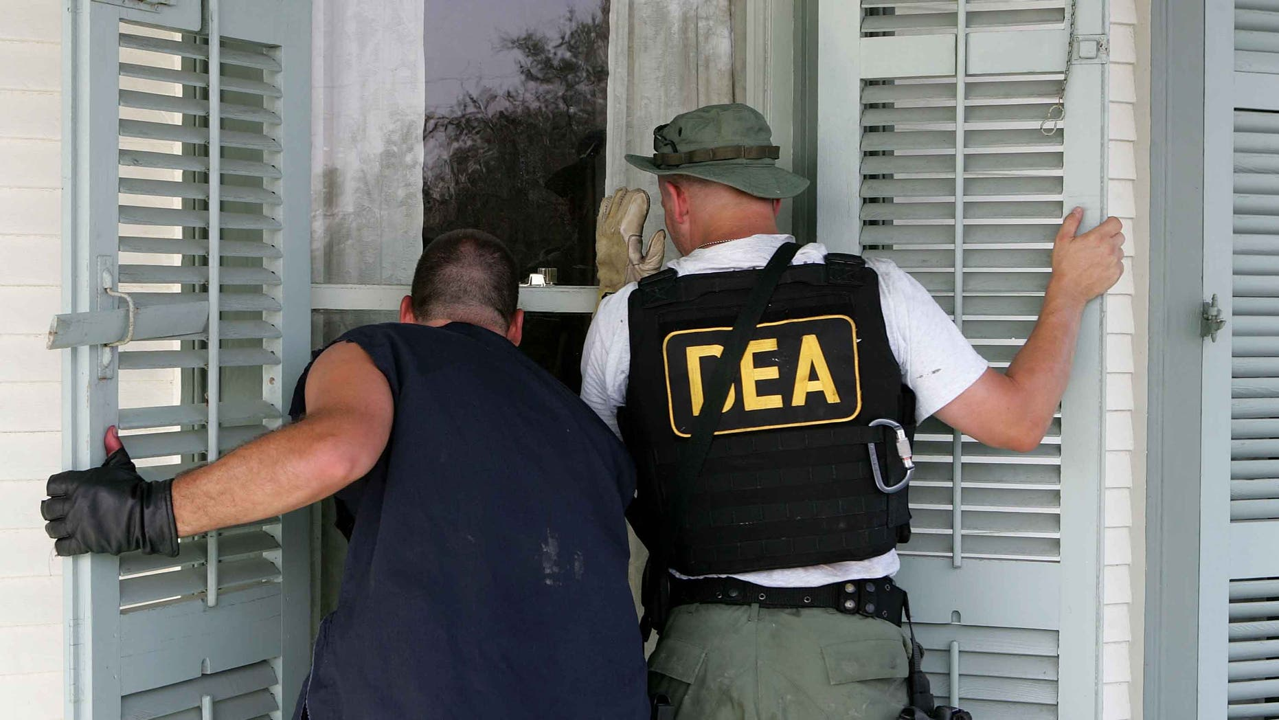 NEW ORLEANS - SEPTEMBER 10:  DEA agents look into a window of a house in the while searching for victims in the Ninth Ward district  September 10, 2005 in New Orleans, Louisiana. Rescue crews continue to search homes searching for hold outs and deceased people.  (Photo by Justin Sullivan/Getty Images)