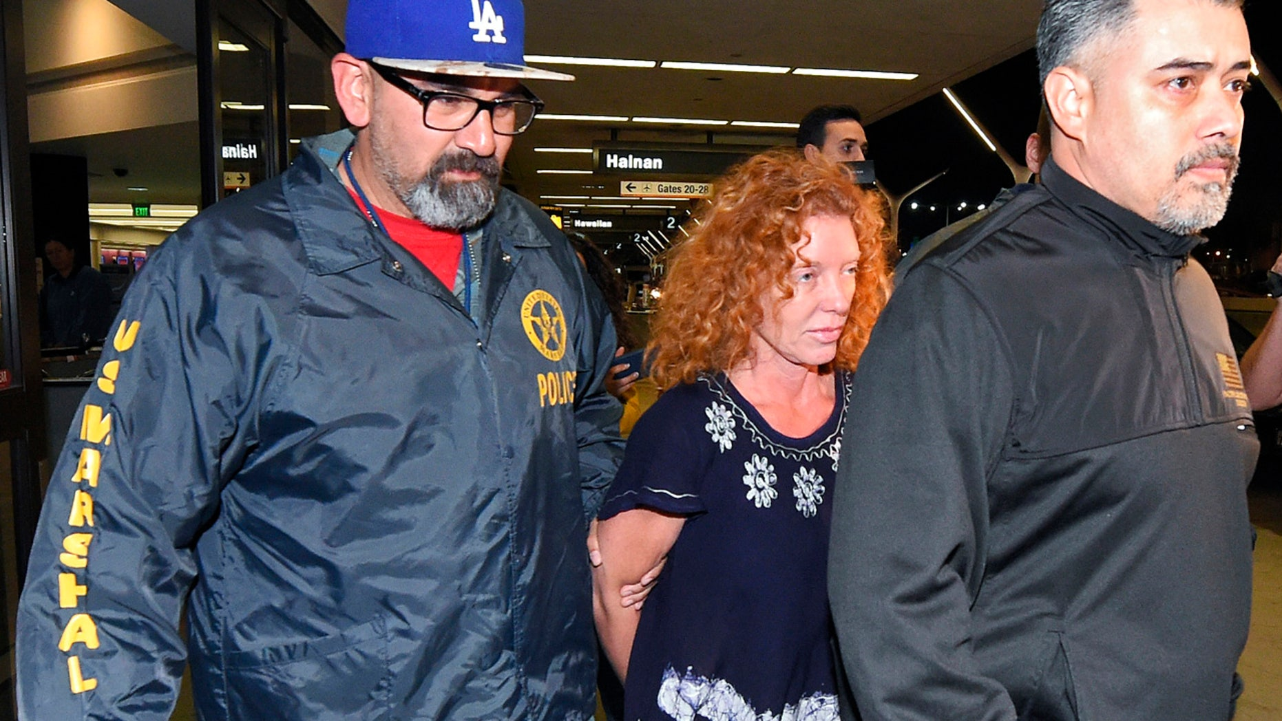 Dec. 31, 2015: Tonya Couch, center, is taken by authorities to a waiting car after arriving at Los Angeles International Airport (AP Photo/Mark J. Terrill)