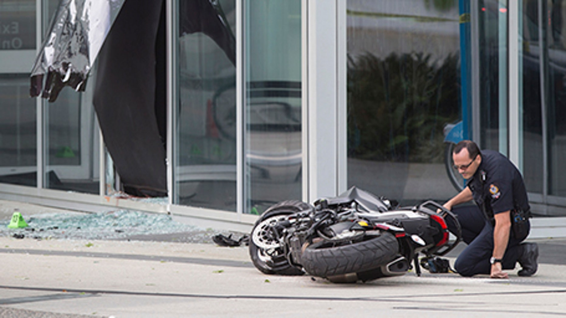"""A police officer examines a motorcycle after a female stunt driver working on the movie """"Deadpool 2"""" died after a crash on set, in Vancouver, B.C., on Aug. 14, 2017. Vancouver police say the driver was on a motorcycle when the crash occurred on the movie set on Monday morning."""