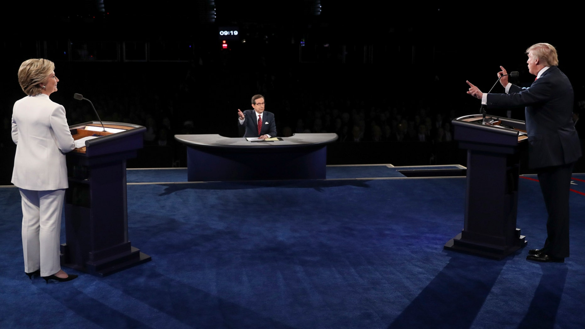 Democratic presidential nominee Hillary Clinton listens as Republican presidential nominee Donald Trump answers a question during the third presidential debate at UNLV in Las Vegas, Wednesday, Oct. 19, 2016. (Joe Raedle/Pool via AP)