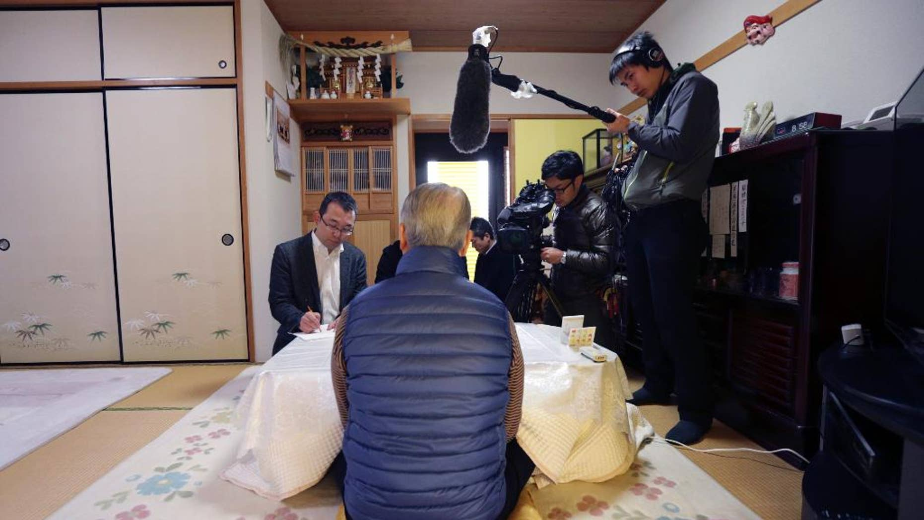 Shoichi Yukawa, center, father of Haruna Yukawa, one of two Japanese hostages held by the Islamic State group, speaks during an interview at his house in Chiba, near Tokyo Sunday, Jan. 25, 2015. Japanese officials are working to verifying a new message purported to be from the Islamic State group holding the hostages. The Associated Press could not verify the contents of the message, which varied greatly from previous videos released by the Islamic State group, which now holds a third of both Syria and Iraq. (AP Photo/Asahi Shimbun, Yasuhiro Sugimoto, Pool)