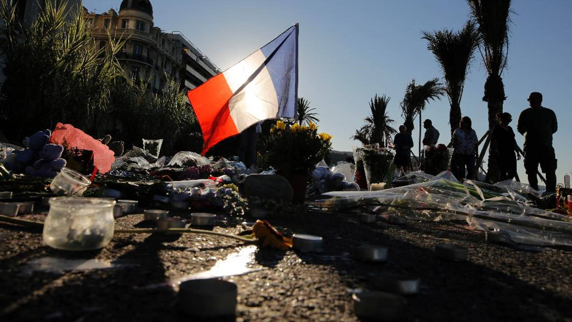 FILE - In this Sunday, July 17, 2016 file photo, a French flag stands among a floral tribute for the victims killed during a deadly attack, on the famed Boulevard des Anglais in Nice, southern France. Residents of the French Riviera city of Nice that lived through the truck rampage horror in July 2016, are reliving it this week following a chillingly similar narrative in Berlin. (AP Photo/Laurent Cipriani, File)