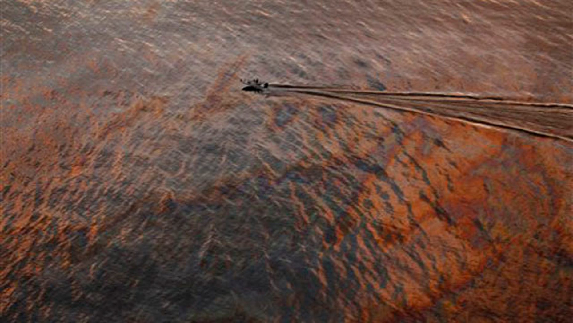 In this July 31 file photo, a boat motors through an oil sheen from the Deepwater Horizon oil spill off the Louisiana coast.