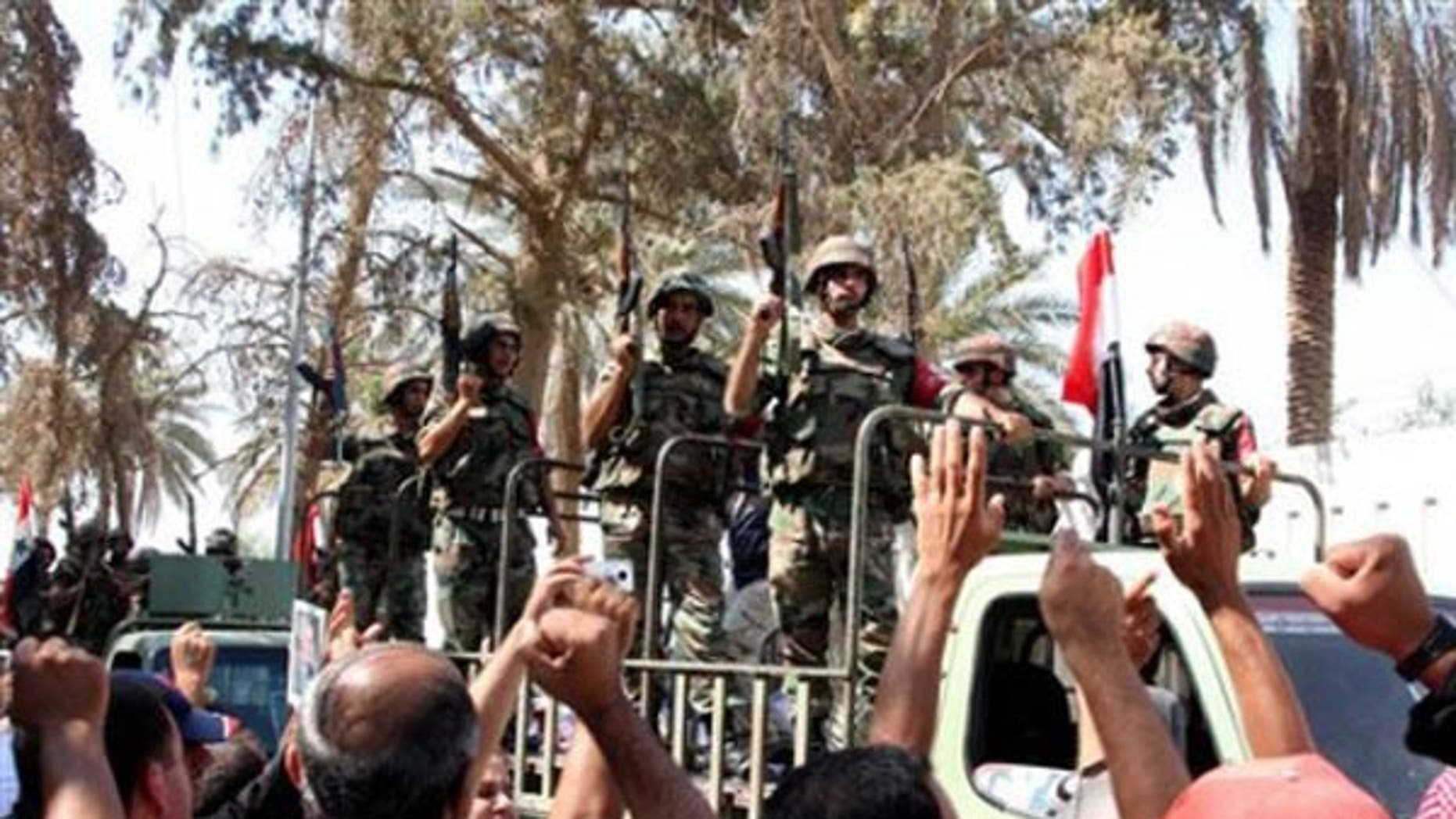 In this photo taken on a government-organized tour, residents cheer Syrian soldiers in Deir el-Zour in 2011.