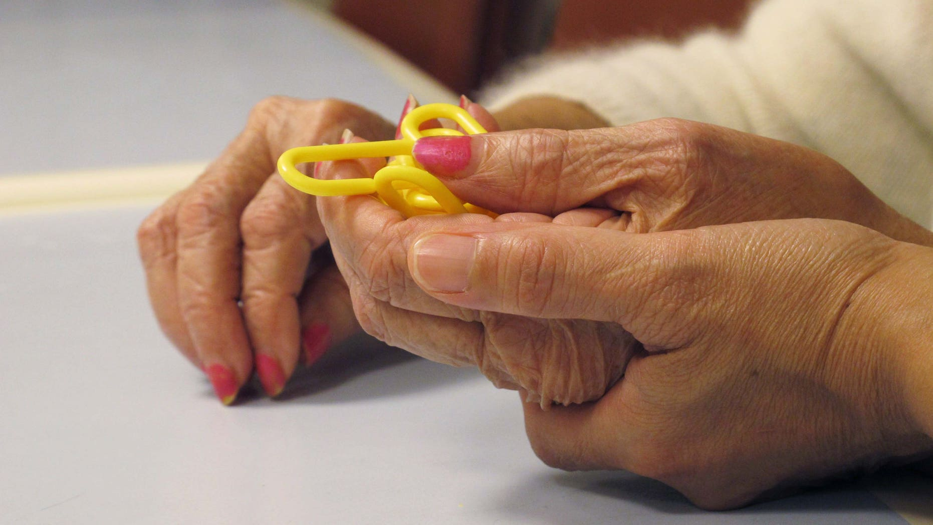 In this Sept. 20, 2012 photo, a physical therapist guides a dementia patient through a puzzle at the Hebrew Home at Riverdale in the Bronx borough of New York. The Hebrew Home has a program that provides care and activity overnight for dementia victims with sleep problems. (AP Photo/Jim Fitzgerald)