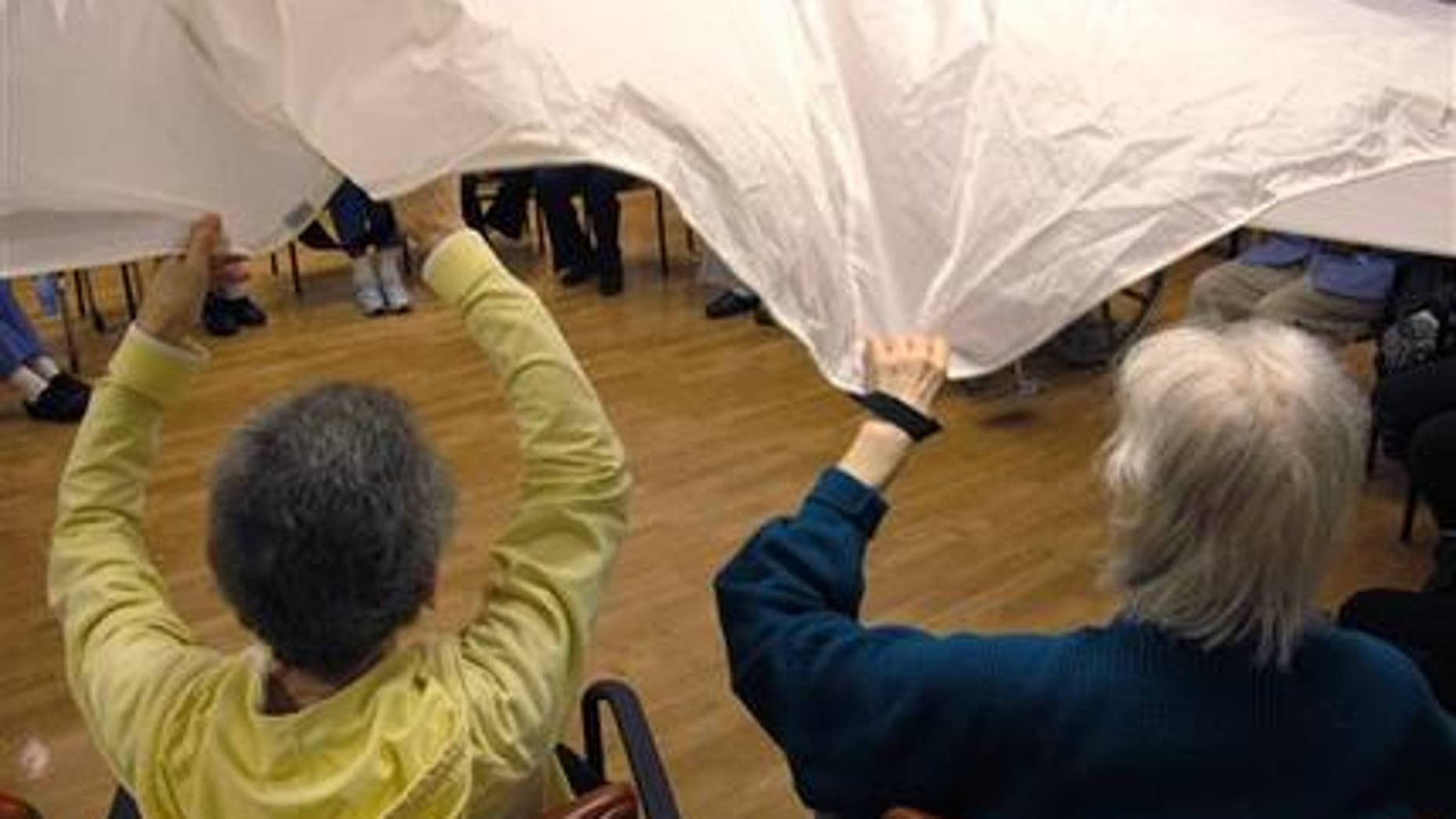 "In this Sept. 20, 2012 photo, dementia patients sitting in a circle formation do an exercise called ""the parachute"" at the Hebrew Home at Riverdale in the Bronx borough of New York. (AP Photo/Jim Fitzgerald)"