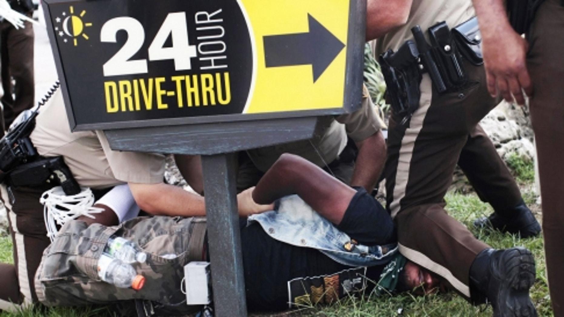 Police officers detain a demonstrator in Ferguson, Mo.