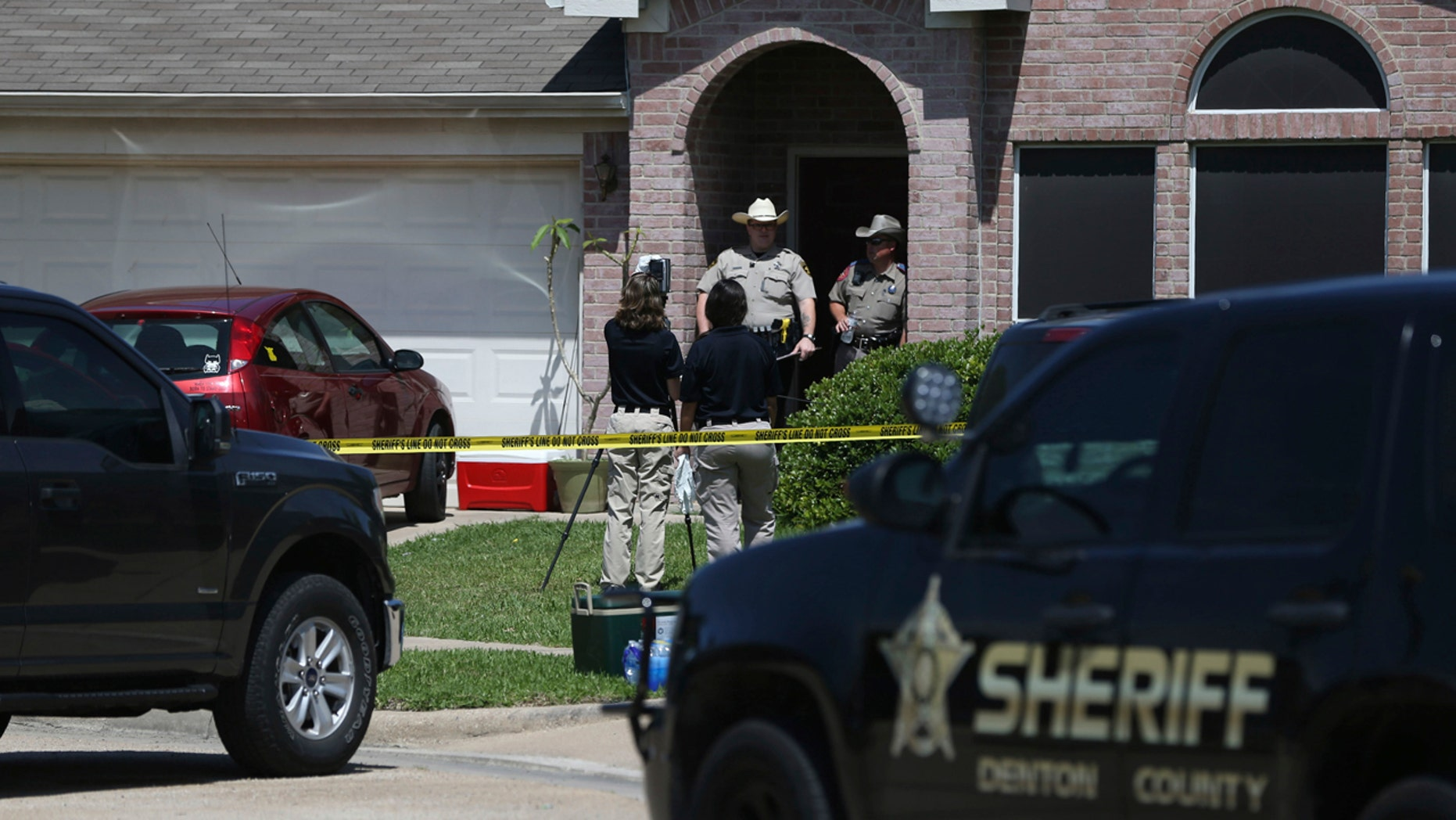 Denton County Sheriff's officers investigate a crime scene at a home where multiple people were killed and one was hospitalized after a shooting in the Remington Park neighborhood of Ponder, Texas, on Wednesday, May 16, 2018.