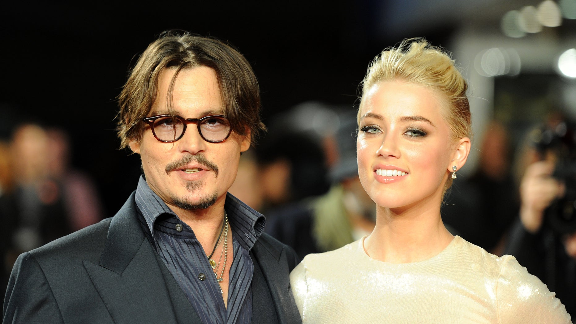 """November 3, 2011. Johnny Depp and Amber Heard pose for photographers as they arrive for the European premiere of """"The Rum Diary"""" in London."""