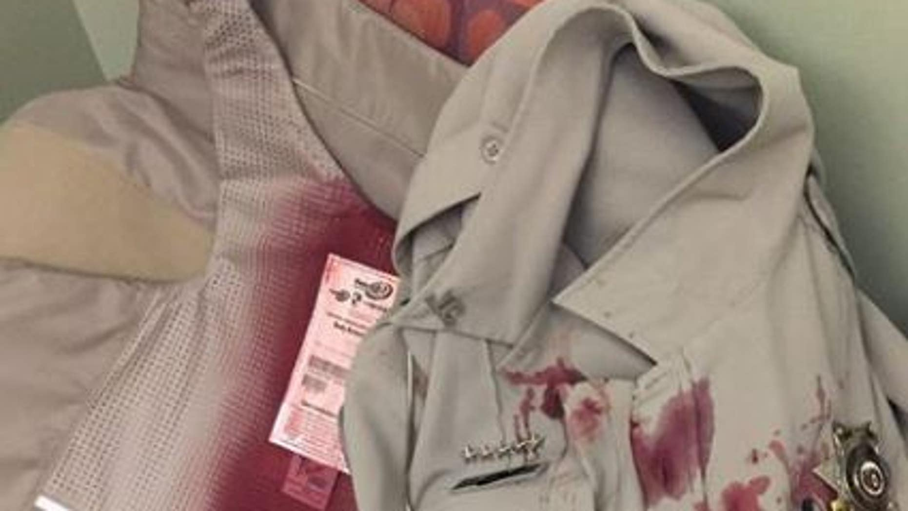 The image shows a Missouri police officer's bload-soaked uniform after he was attacked by a dog while serving a civil summons on Tuesday.