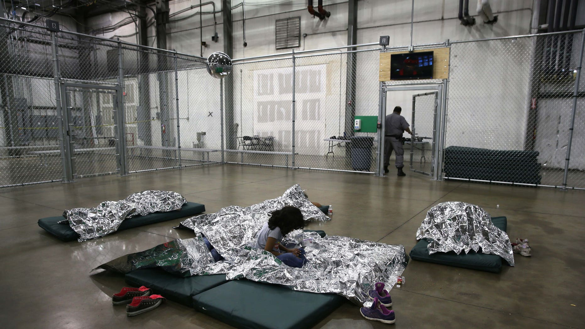 MCALLEN, TX - SEPTEMBER 08:  A girl from Central America rests on thermal blankets at a detention facility run by the U.S. Border Patrol on September 8, 2014 in McAllen, Texas. The Border Patrol opened the holding center to temporarily house the children after tens of thousands of families and unaccompanied minors from Central America crossed the border illegally into the United States during the spring and summer. Although the flow of underage immigrants has since slowed greatly, thousands of them are now housed in centers around the United States as immigration courts process their cases.  (Photo by John Moore/Getty Images)