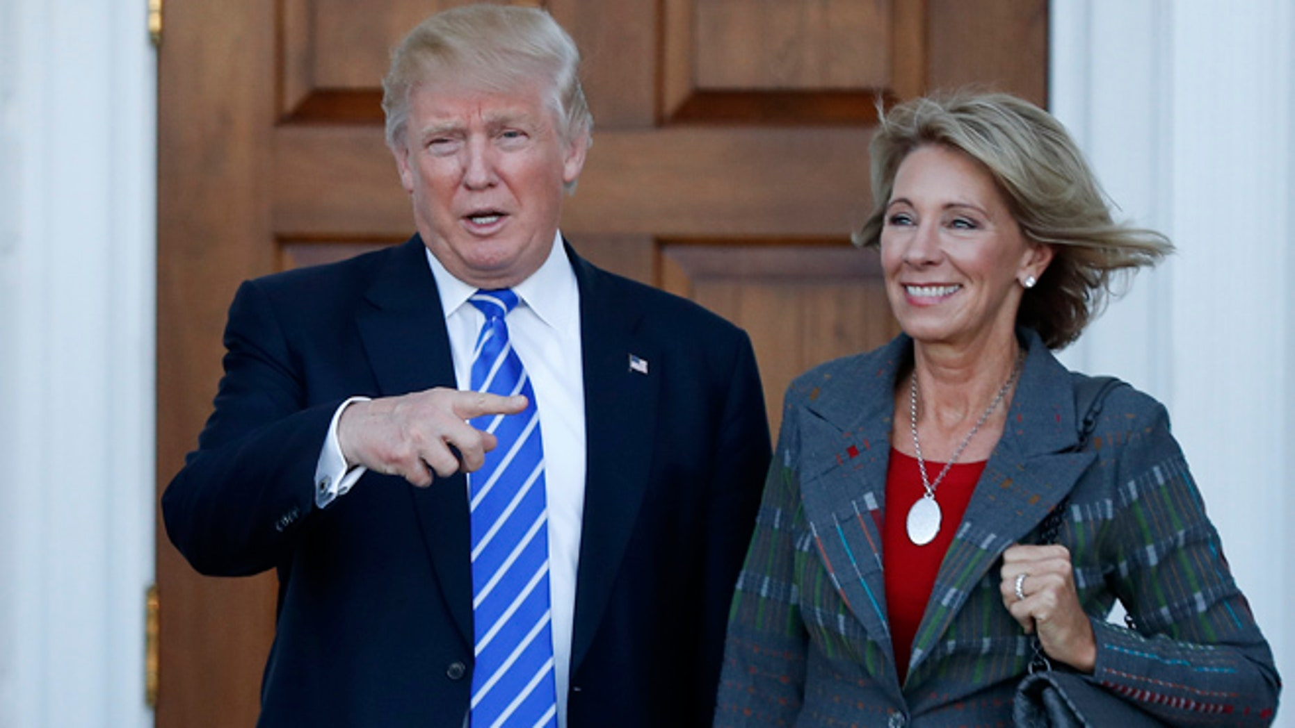 FILE - In this Nov. 19, 2016 photo, President-elect Donald Trump and Betsy DeVos pose for photographs at Trump National Golf Club Bedminster clubhouse in Bedminster, N.J. Trump has chosen charter school advocate DeVos as Education Secretary in his administration.