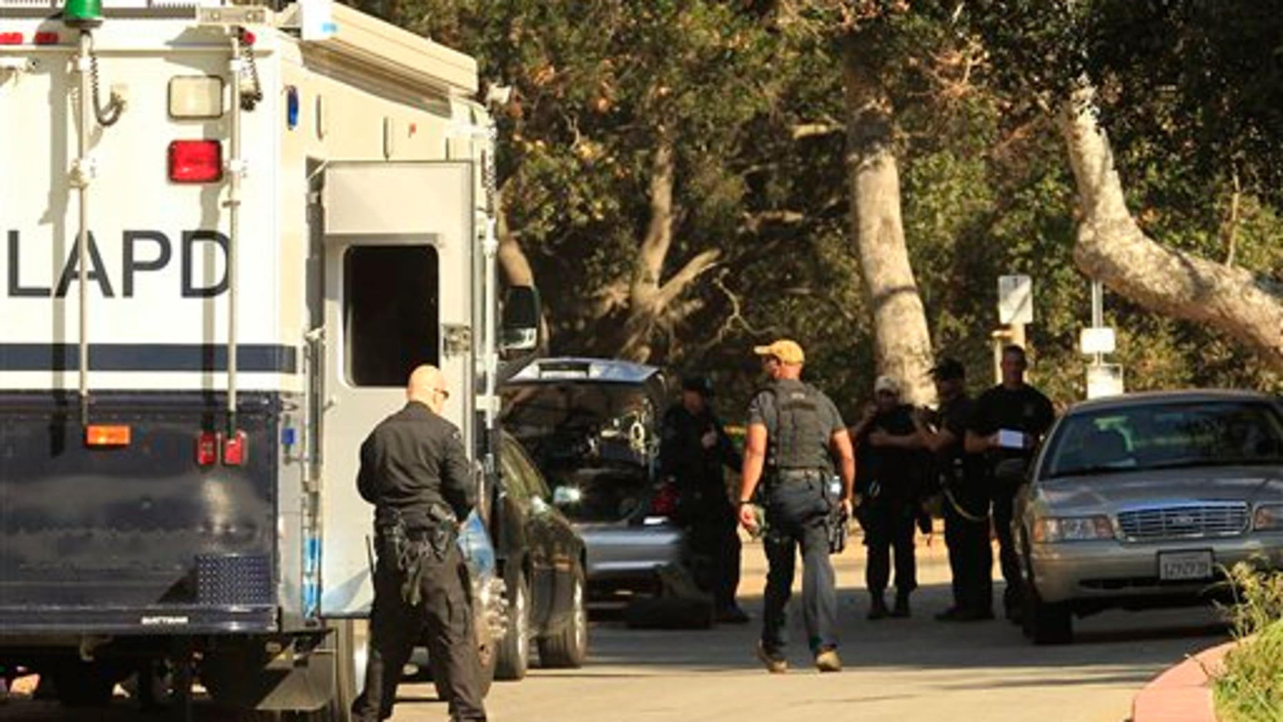 January 18, 2012: Los Angeles Police detectives work a crime scene in Griffith Park off Canyon Drive after a human head was discovered off a nearby trail Tuesday by two women walking their dogs in Los Angeles. A human hand has since been discovered. (AP Photo/Los Angeles Times, Al Seib, Pool)