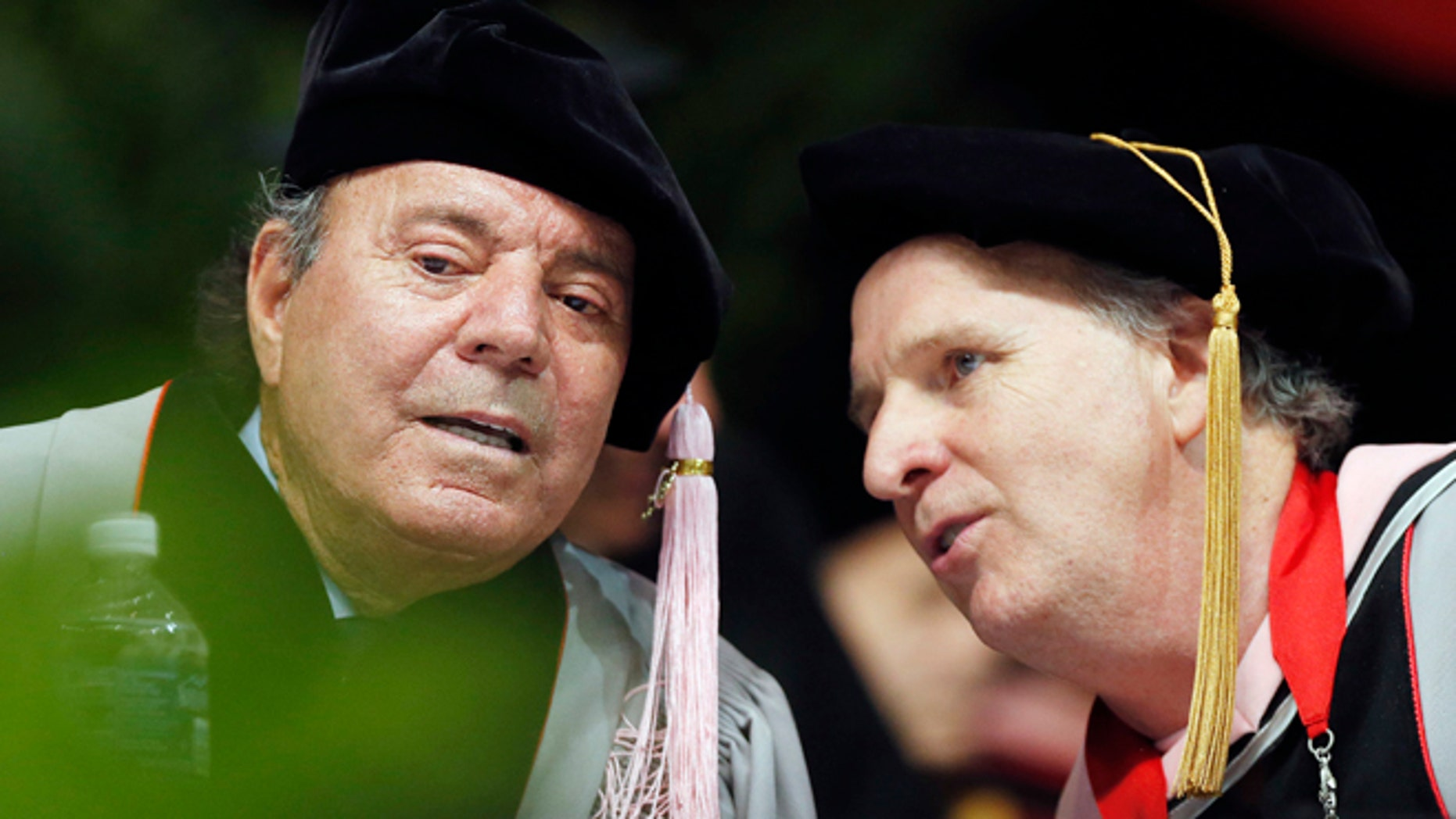 Julio Iglesias, left,  speaks with Berklee College of Music president Roger Brown before receiving an honorary doctor of music degree during commencement ceremonies, Saturday, May 9, 2015, in Boston. (AP Photo/Michael Dwyer)