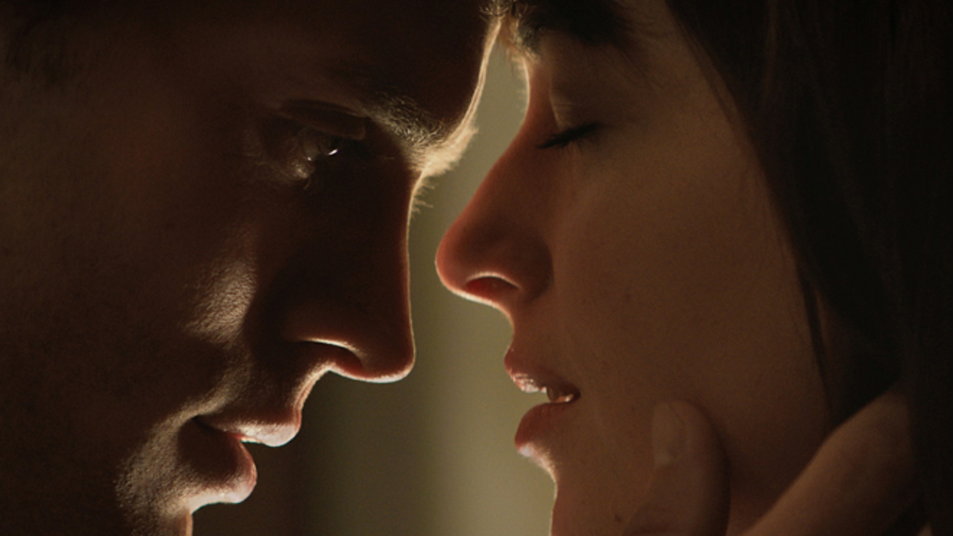 """In this image released by Universal Pictures and Focus Features, Jamie Dornan, left, and Dakota Johnson appear in a scene from """"Fifty Shades of Grey."""" The ticket-buying site Fandango said pre-sales have propelled the movie into the 15-year-old company's Top 5 for R-rated selections. Several hundred screenings have already sold out from Tupelo, Mississippi, to Chattanooga, Tennessee, the company said. (AP Photo/Universal Pictures and Focus Features)"""