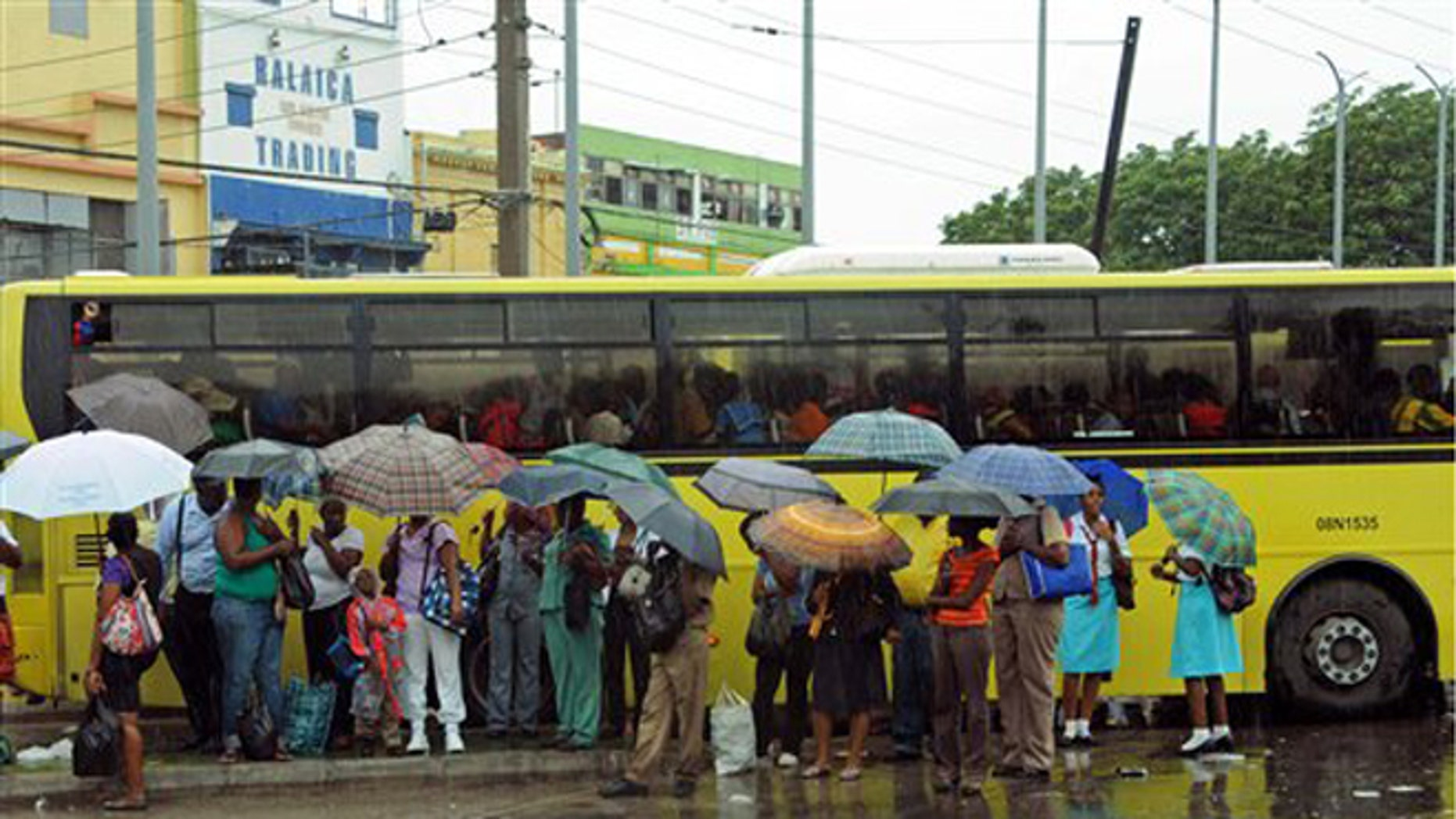 Commuters wait at a bus stop as rain brought by the outer bands of Tropical Storm Sandy falls in Kingston, Jamaica, Tuesday, Oct. 23, 2012. The U.S. National Hurricane Center in Miami said Sandy was expected to become a hurricane as it nears Jamaica on Wednesday. (AP Photo/Collin Reid)