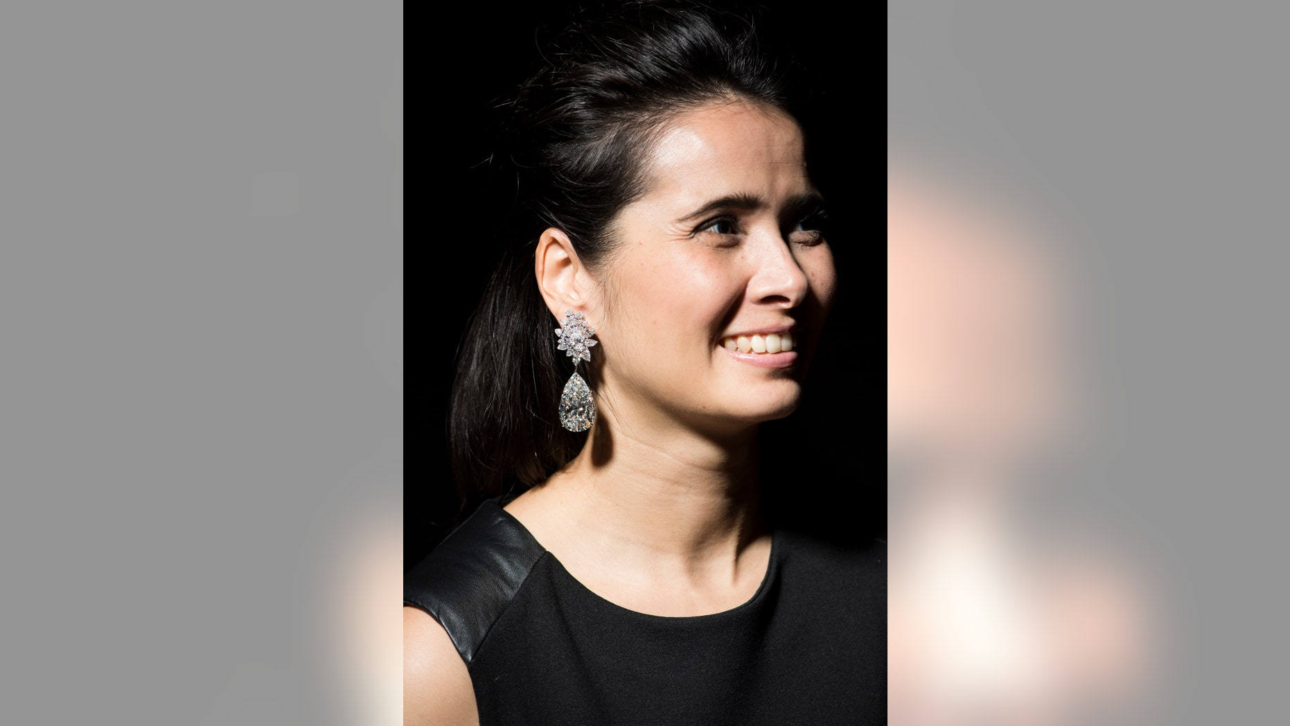 """A model displays a pair of stunning diamond earrings """"Miroir de l'Amour"""" weighing 52.55 and 50.47 carats during a Christie's press preview in Geneva, Switzerland, Thursday, Nov. 10, 2016."""
