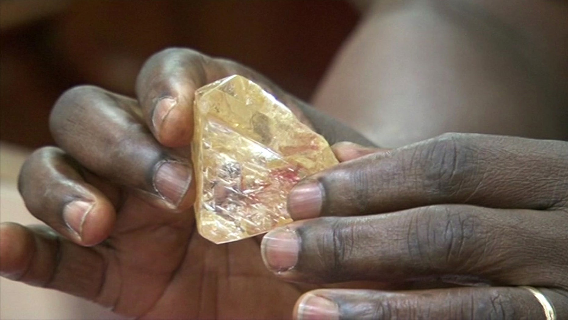 In this photo taken from video footage, Sierra Leone's President Ernest Bai Koroma hands a diamond during a meeting with delegates of Kono district, where the gem was found, at the presidential office in Freetown, Sierra Leone, Thursday, March 16, 2017