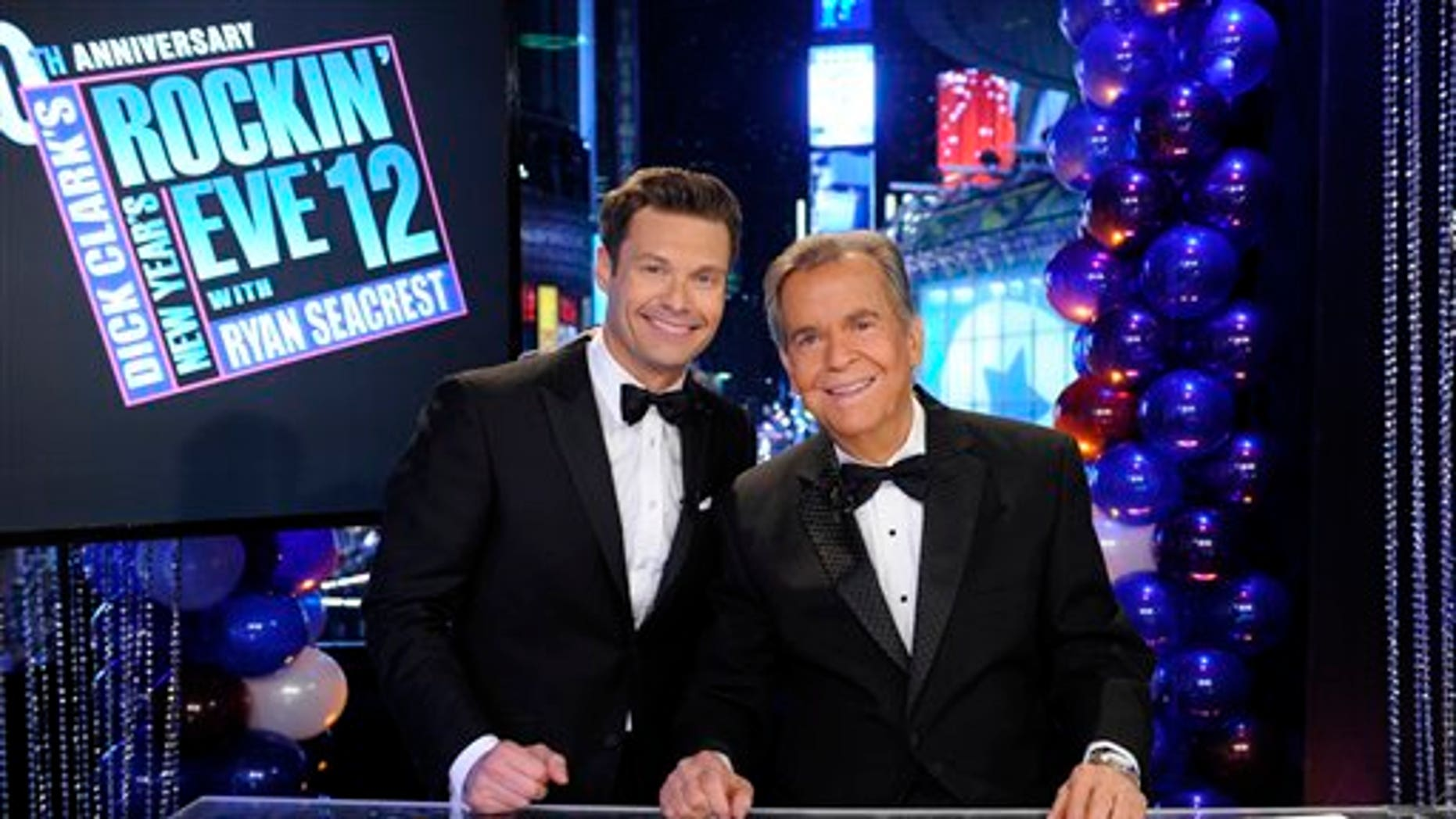 """In this Dec. 31, 2011 photo released by ABC, hosts Dick Clark, right, and Ryan Seacrest pose on the set of """"Dick Clark's New Year's Rockin' Eve with Ryan Seacrest 2012"""" in Times Square in New York.  (AP Photo/ABC, Ida Mae Astute)"""