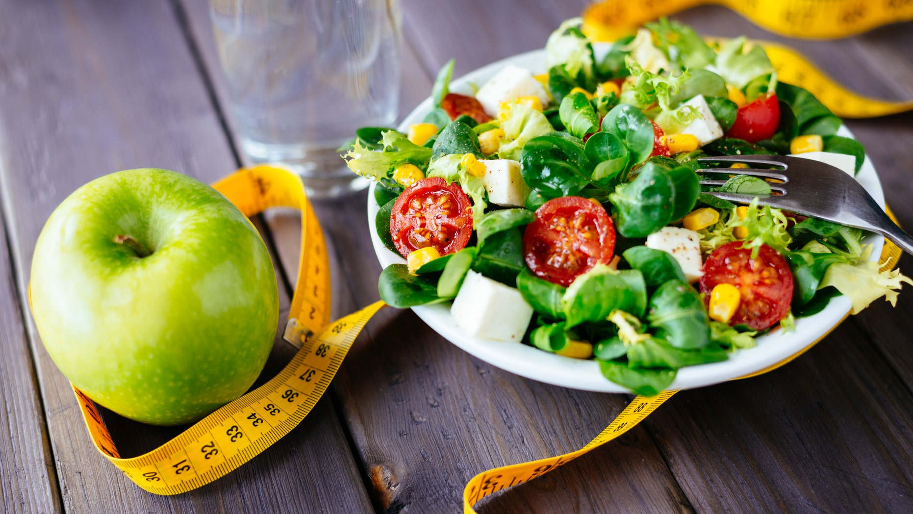 Fitness salad and apple fruit surrounded by measuring tape on rustic wooden table. Mixed greens, tomatos, diet cheese, olive oil and spices for healthy lifestyle concept.