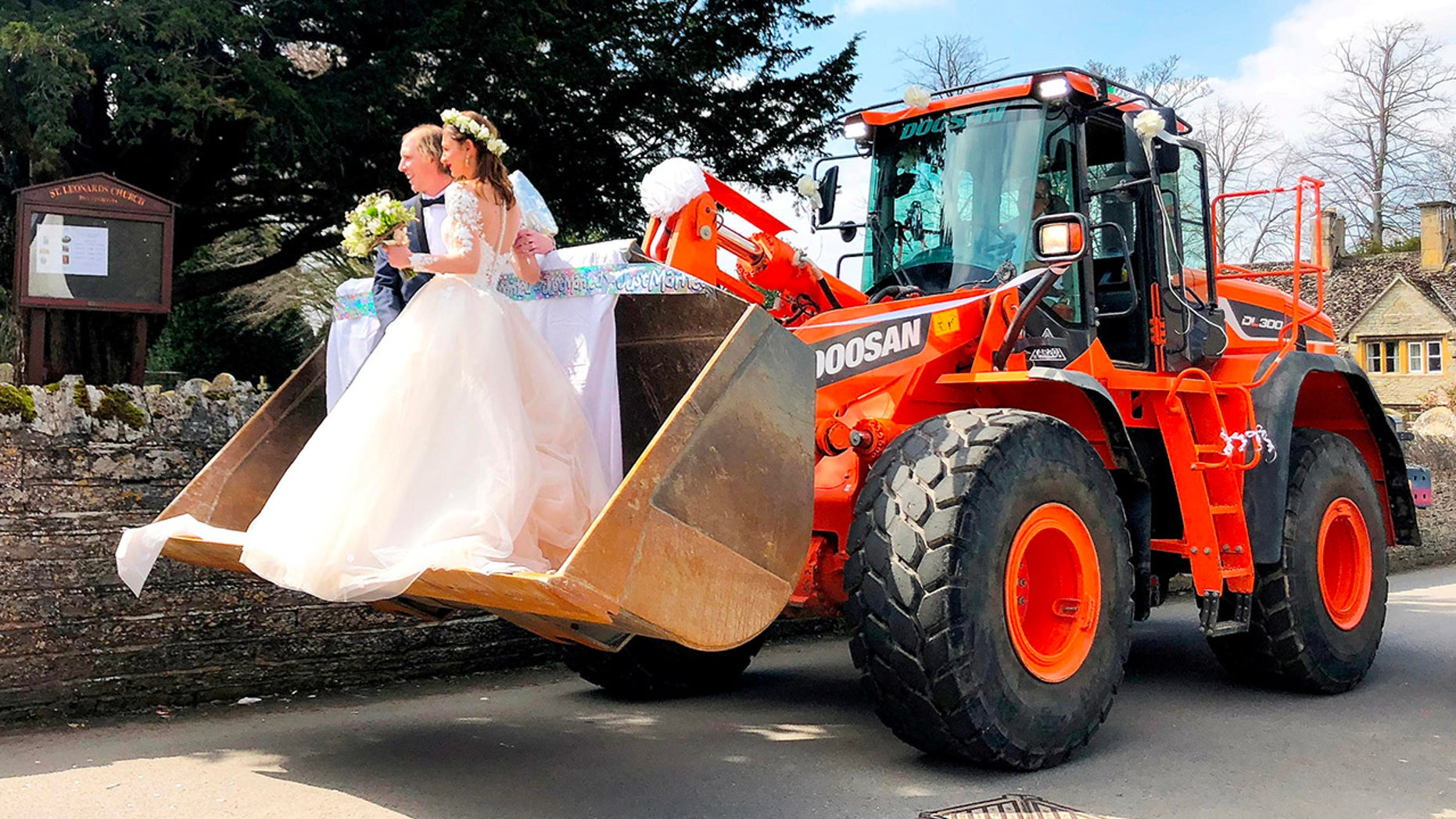 A JCB driver and his new bride stunned guests when they turned up to their wedding reception – in the bucket of a giant DIGGER.  See NTI story NTIWED.  Jason Smith, 29, and his bride Iona, 28, ditched the traditional horse-drawn carriage and opted instead for an 18 ton earth mover.  They arrived at their wedding at Bretforton Church, Evesham, Worcs., on Saturday (5/4) in the digger in front of friends and family.  Jason's colleagues at local firm Budget Skips organised the transport as a surprise for him and new wife Iona.