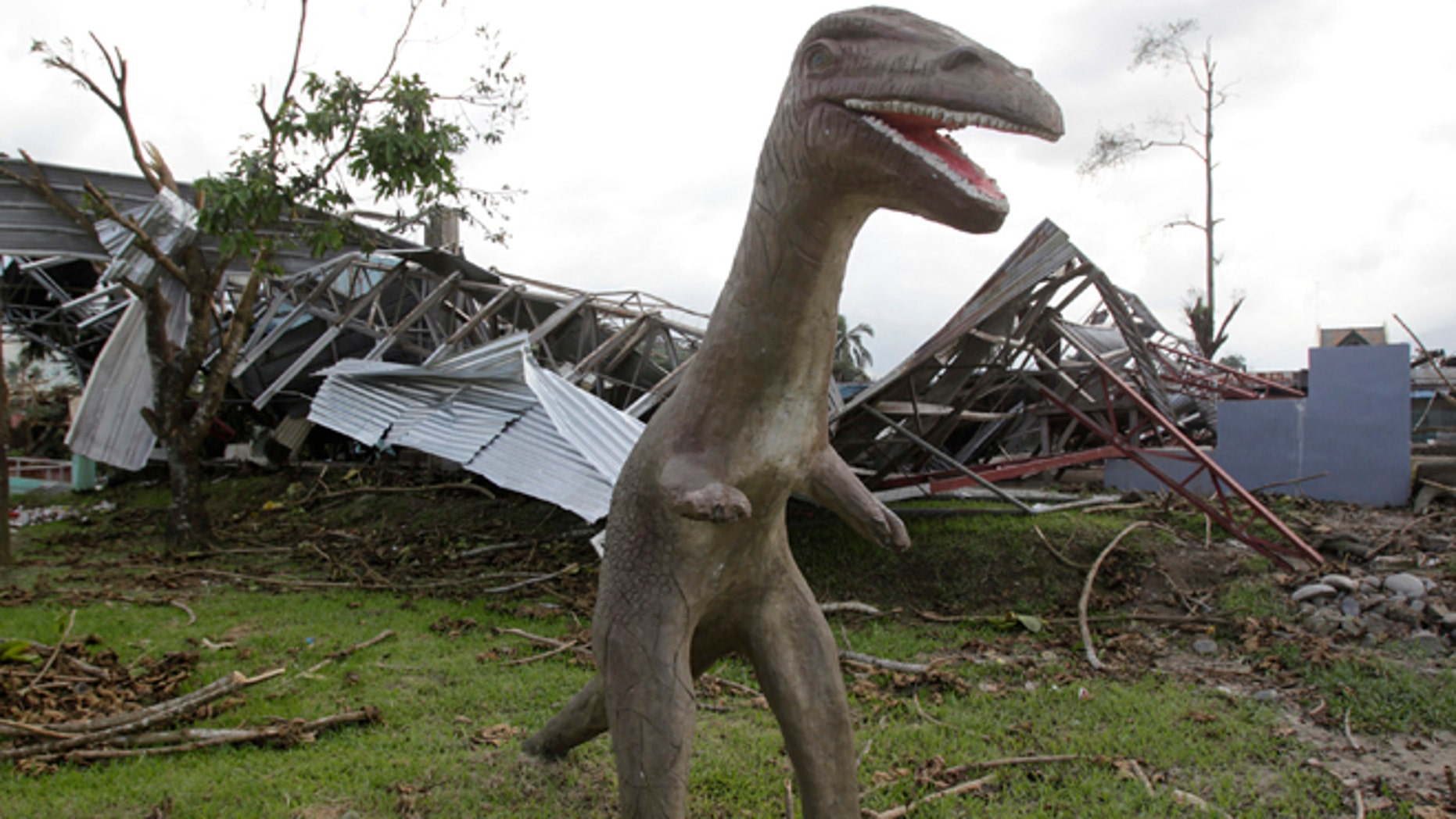 A concrete-made dinosaur statue stands next to a building destroyed by strong winds brought about at the height of Typhoon Bopha last Tuesday, at a playground in New Bataan town in Compostela Valley, southern Philippines December 9, 2012. A much-weakened storm was set to make landfall in the Philippines' northwest on Sunday, five days after the year's strongest typhoon, Typhoon Bopha, killed 540 people and caused crop damage worth about 8 billion pesos in the south. Residents in typhoon-hit areas on southern Mindanao island have been appealing for food, water and other relief supplies. REUTERS/Erik De Castro (PHILIPPINES - Tags: DISASTER ENVIRONMENT SOCIETY)