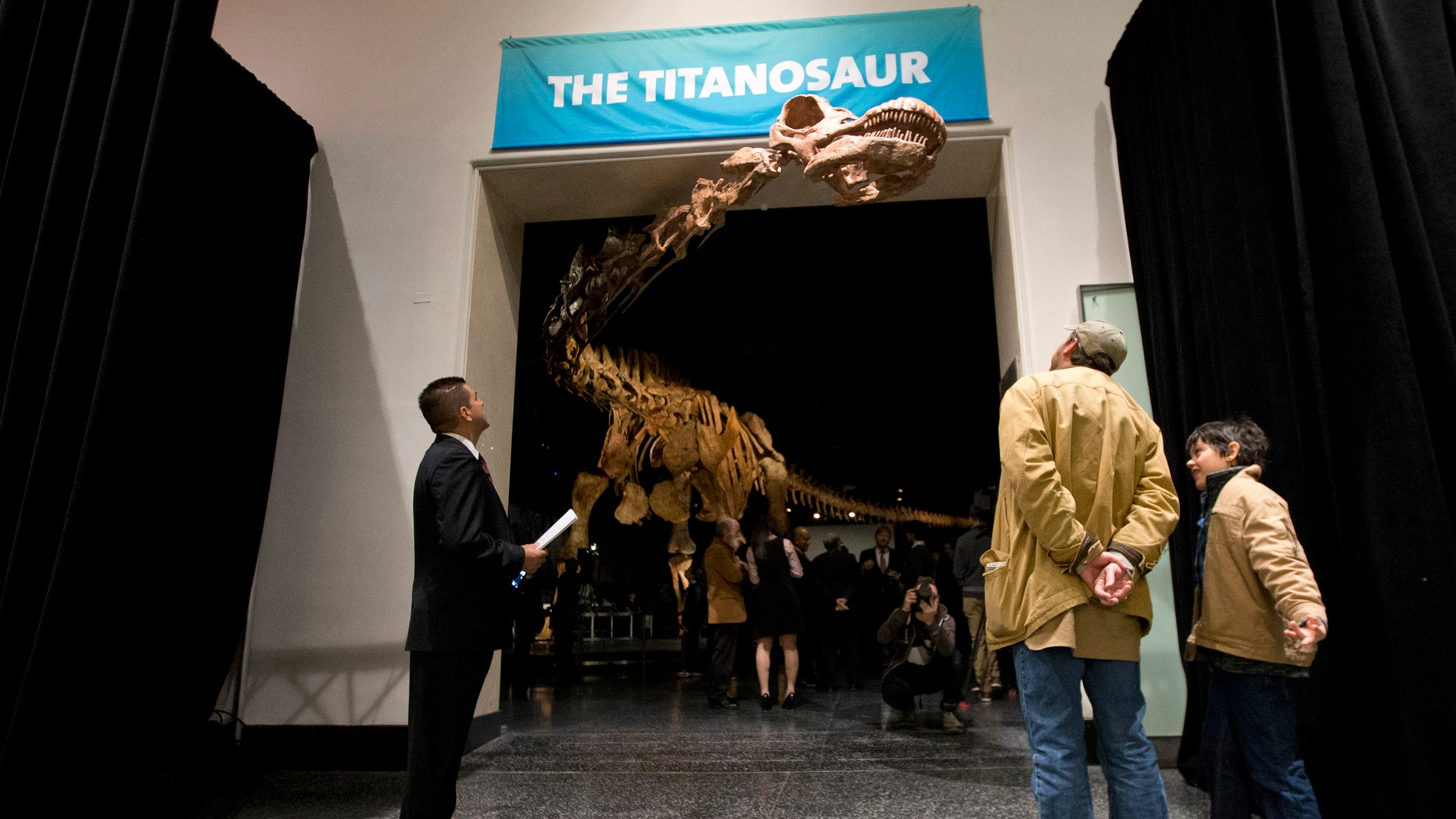 File-This Jan. 14, 2016, file photo shows visitors to the American Museum of Natural History examining a replica of a 122-foot-long dinosaur on display. A study proclaims a newly named species the heavyweight champion of all dinosaurs. (AP Photo/Mary Altaffer, File)