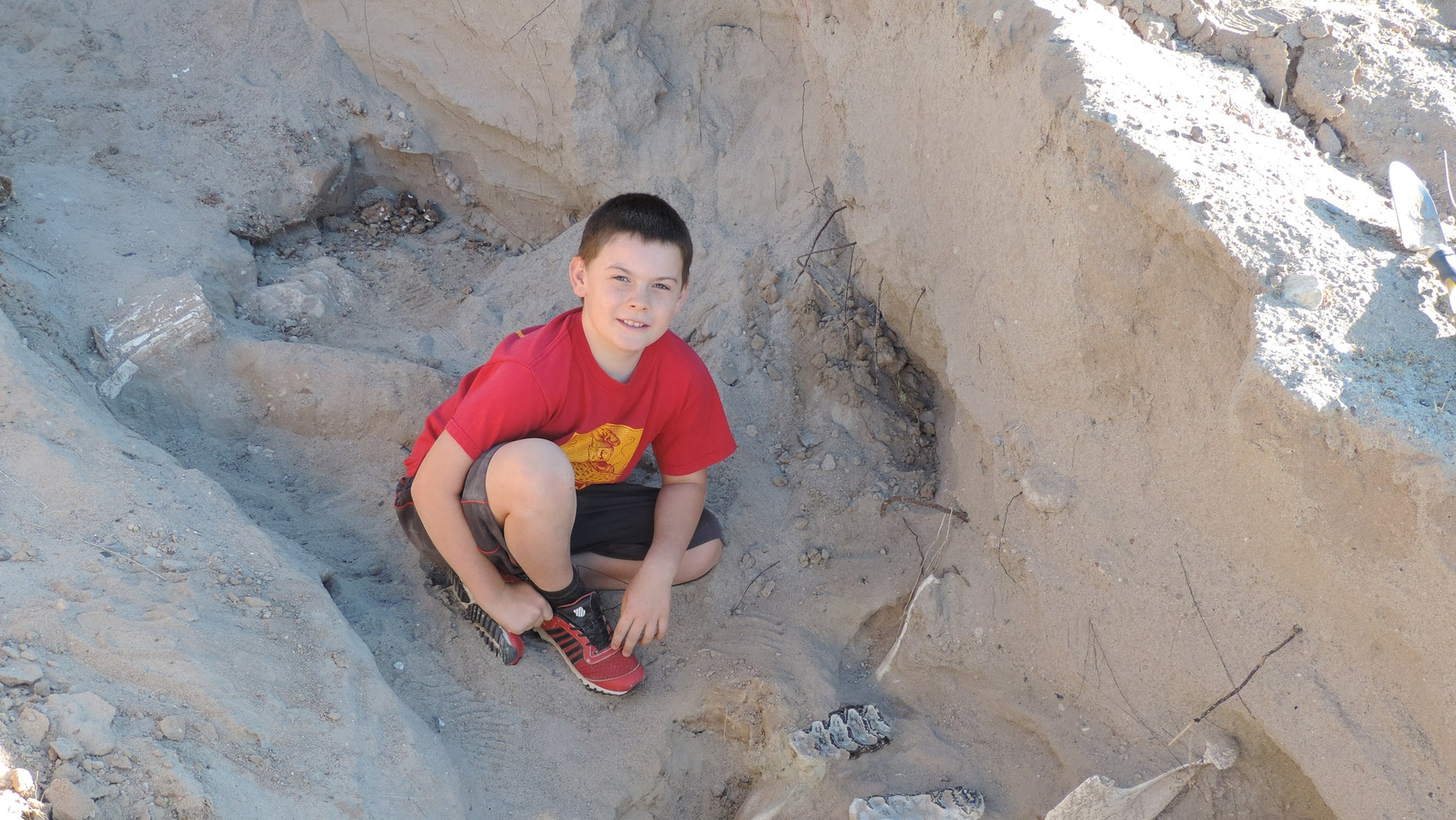 Jude Sparks with the dinosaur fossil (Credit: Peter Houde)