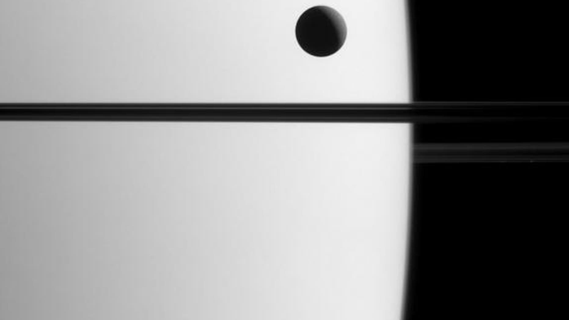 Saturn's moon Dione crosses the face of the ringed planet in an image obtained on May 21, 2015.