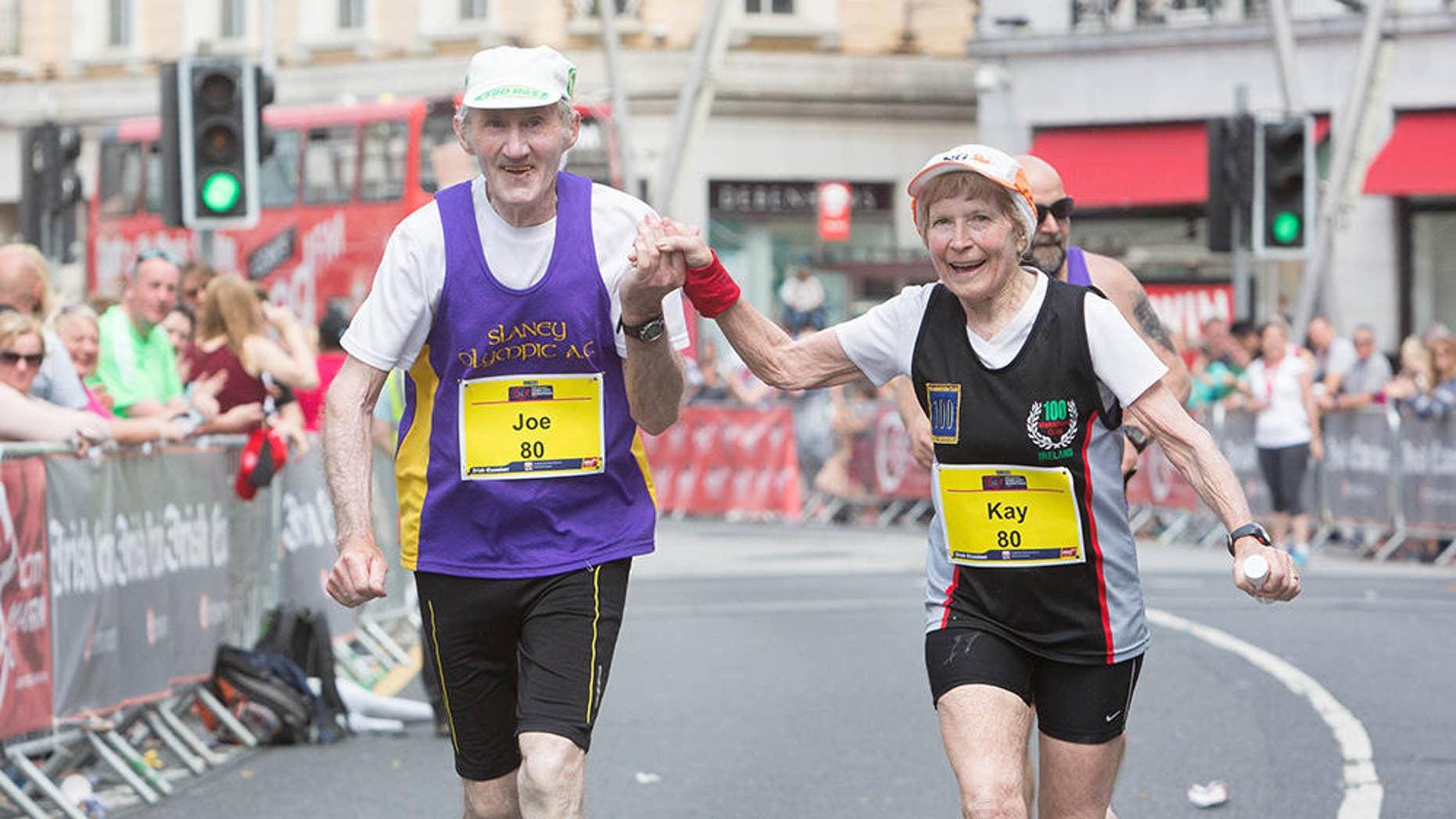 Kay and Joe O'Regan grasp hands as they approach the finish line of the 2016 Cork City Marathon. (photograph courtesy of Cork City Marathon)