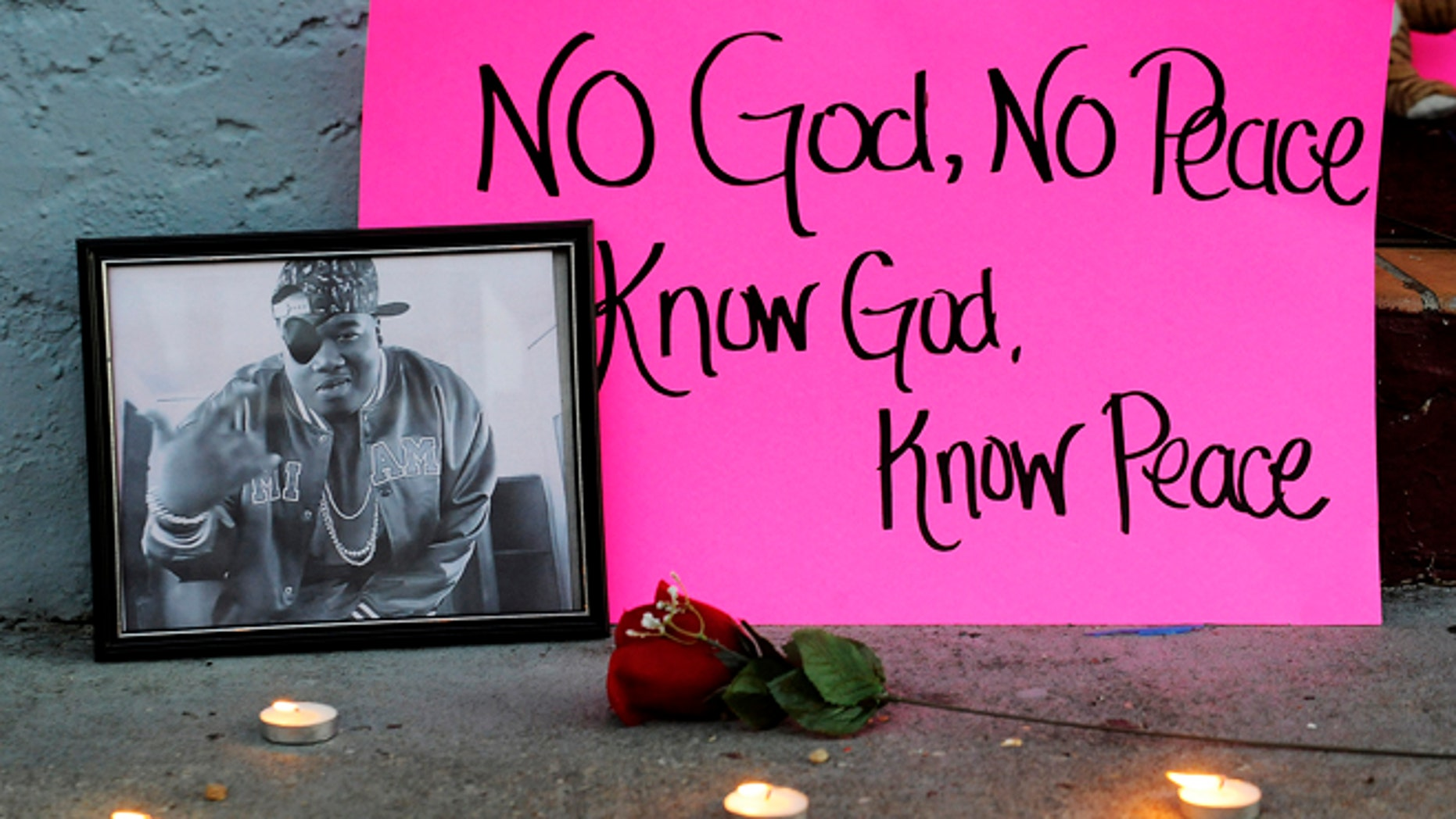 """Dec. 29, 2013: A photo of slain rapper Glenn """"Doe B."""" Thomas sits on a sidewalk Sunday, Dec. 29, 2013, at a candlelight vigil for victims of a fatal shooting at Centennial Hill Bar and Grill in Montgomery, Ala."""