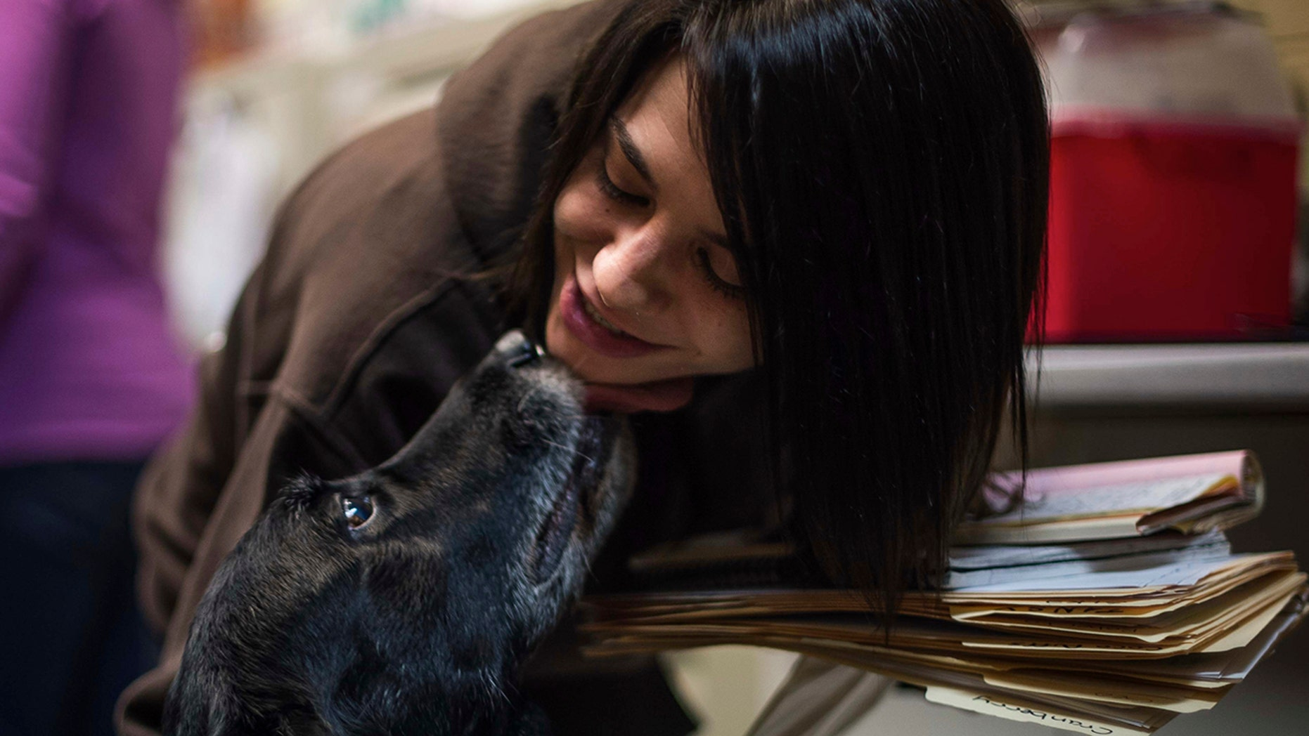 Jody Berisko, an employee at Animal Protectors of Allegheny Valley gets a kiss from Abby on Jan. 30, 2018.