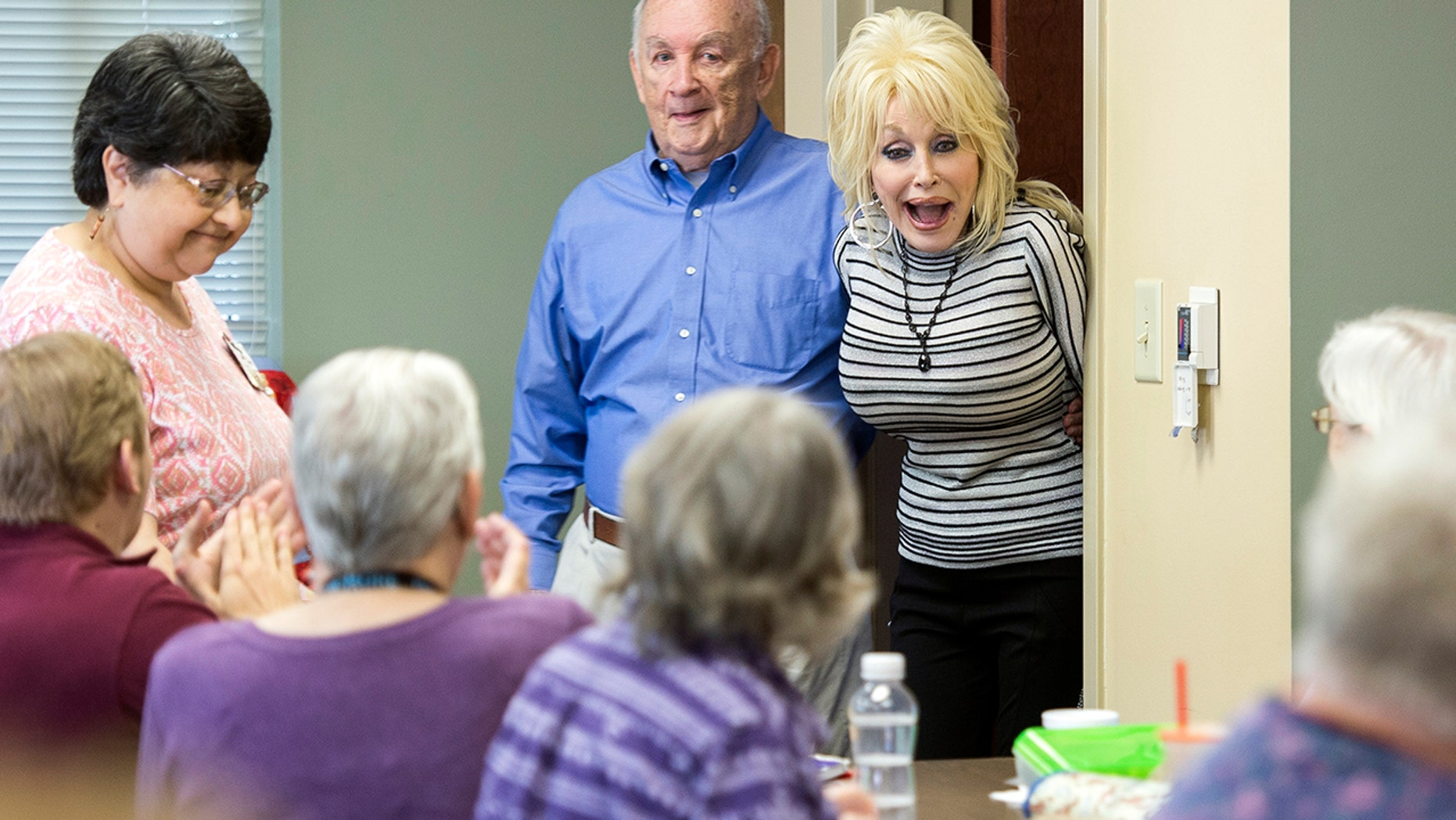 Country music superstar Dolly Parton, back right, surprises a quilting class at the renamed My People Senior Activity Center in Sevierville, Tenn., Monday, May 7, 2018. Parton came for a dedication ceremony Monday to rename the facility in honor of her parents, Robert and Avie Lee Parton.